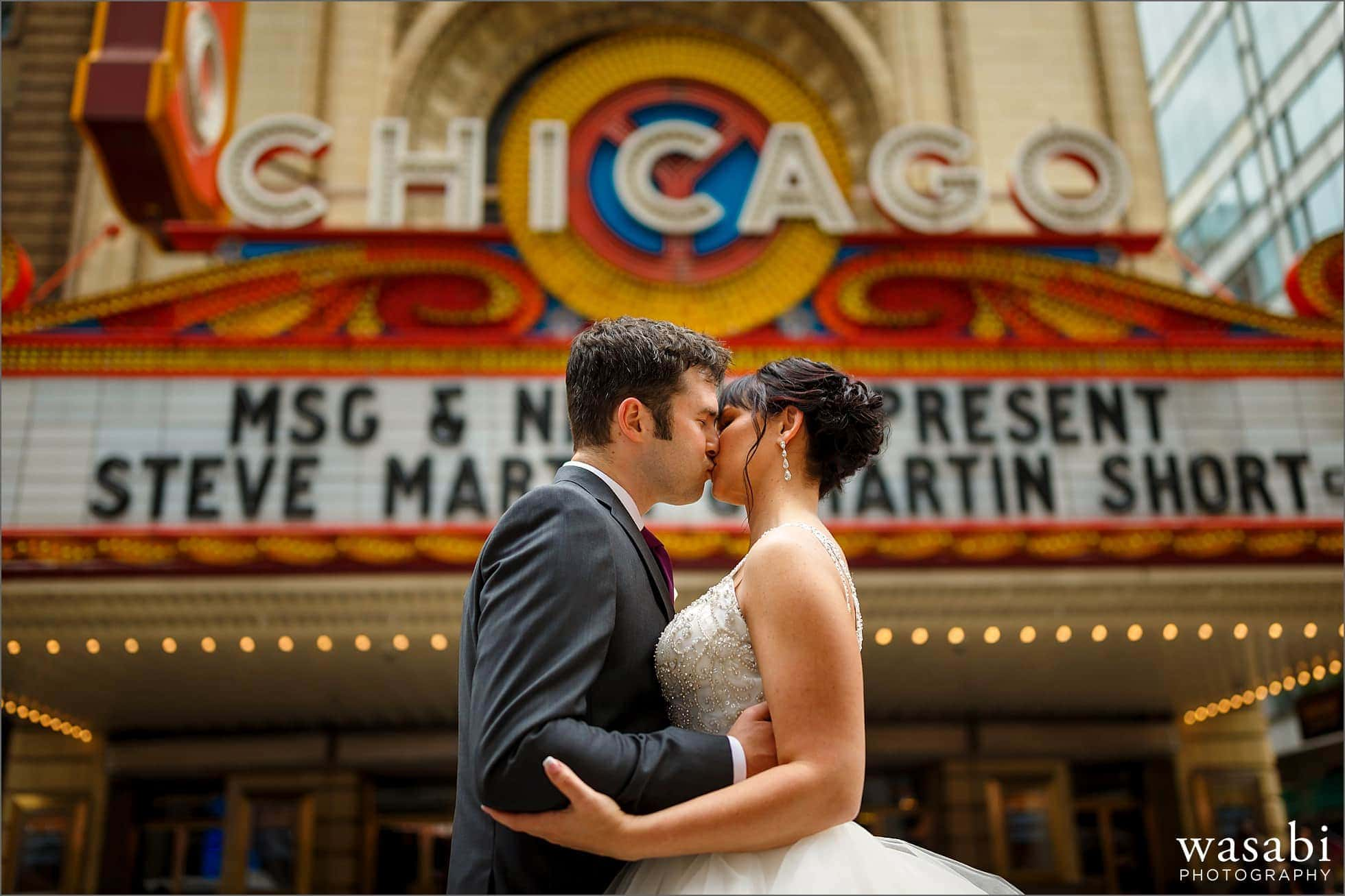 bride and groom kiss for wedding photo in front of Chicago Theatre sign