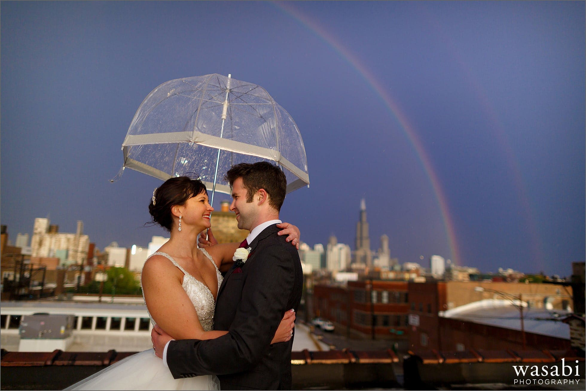 bride and groom pose for a chicago skyline rainbow wedding photo under an umbrella on the rooftop of Room 1520