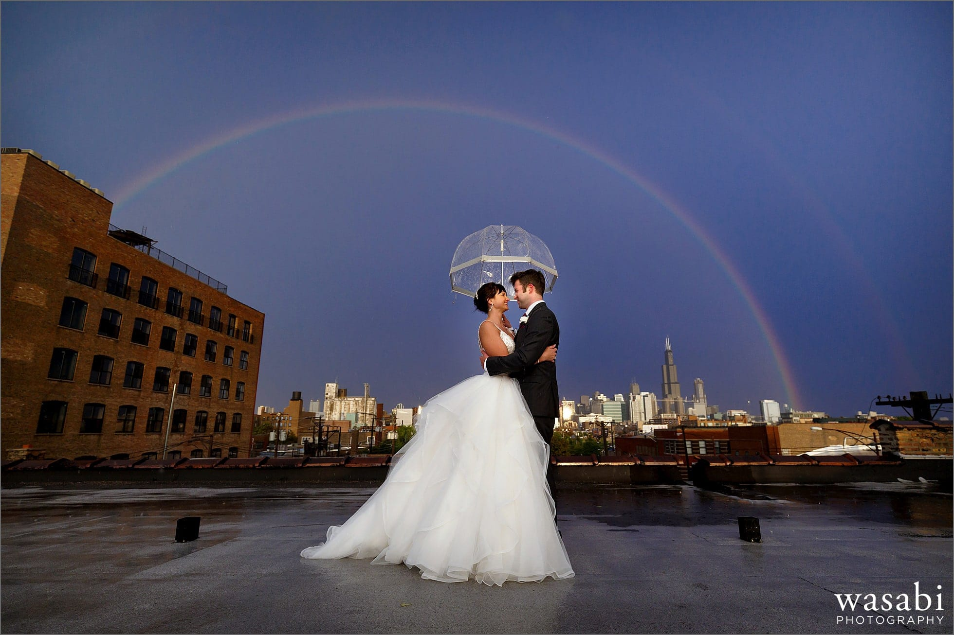 bride and groom pose for a wide angle chicago skyline rainbow wedding photo under an umbrella on the rooftop of Room 1520