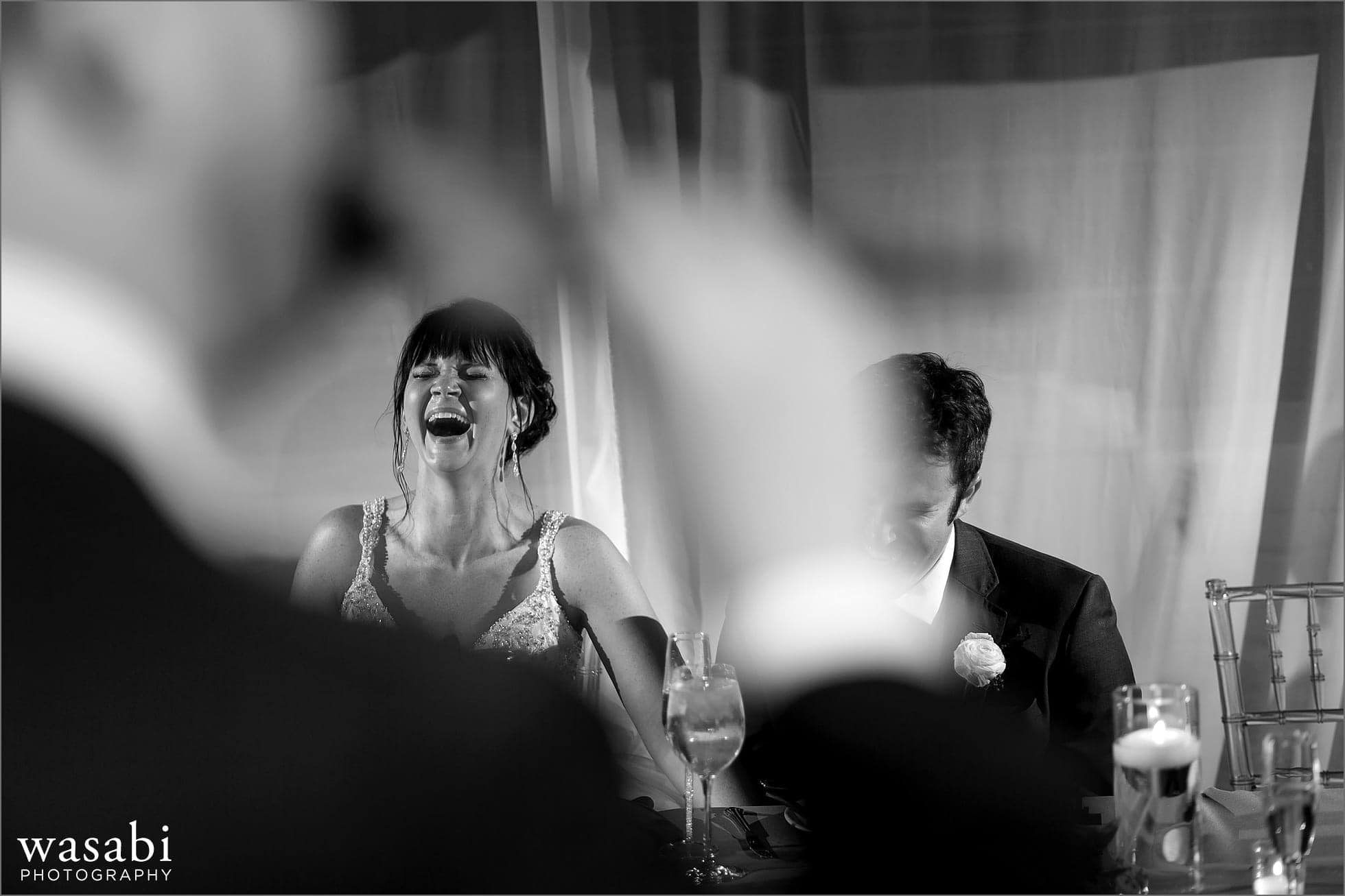 bride and groom react to groomsmen playing pan flute during toast at wedding reception at Room 1520 in Chicago
