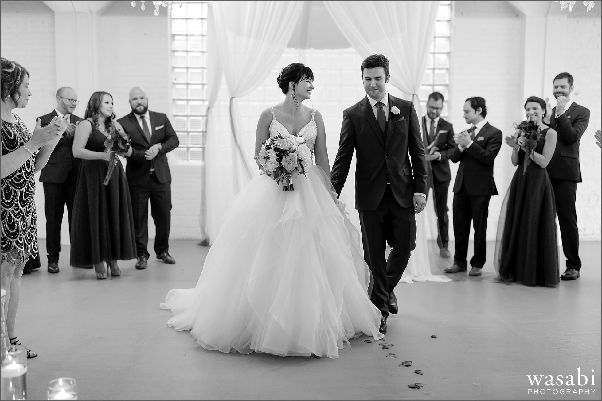 bride and groom walk back down the aisle together after wedding ceremony at Room 1520 in Chicago