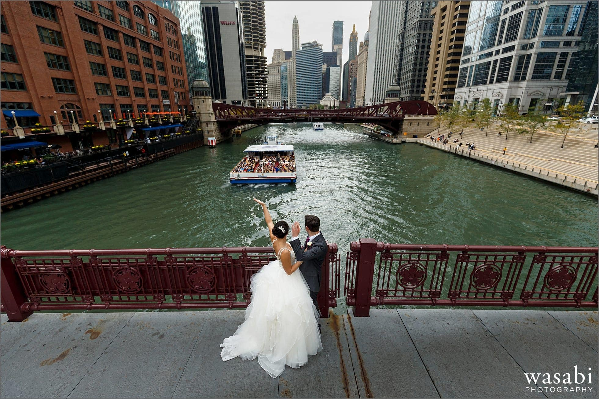 bride and groom wave to water taxi on LaSalle Street bridge above the Chicago river