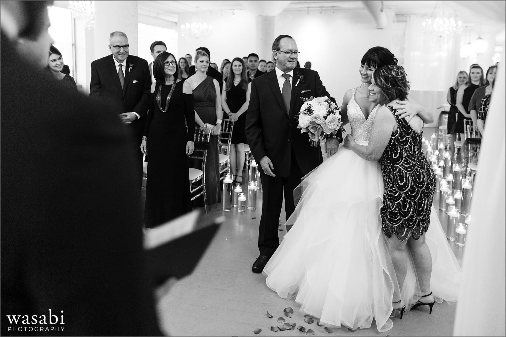 bride hugs her parents after walking down the aisle with her father during wedding ceremony at Room 1520 in Chicago