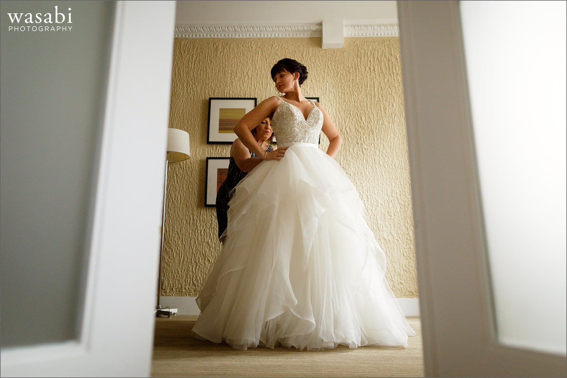 brides mom helps her into dress while getting ready for her wedding at Raffaello Hotel in Chicago