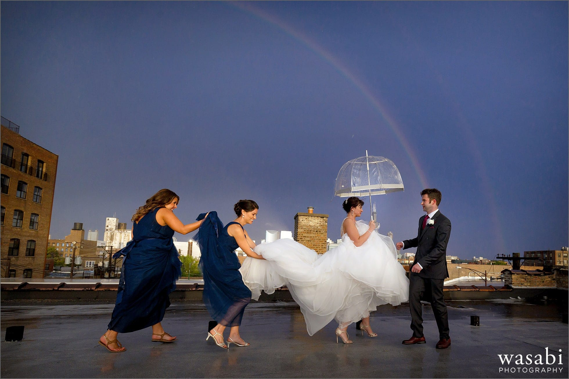 bridesmaids help bride with dress under a rainbow on the roof for Room 1520 wedding photos in Chicago