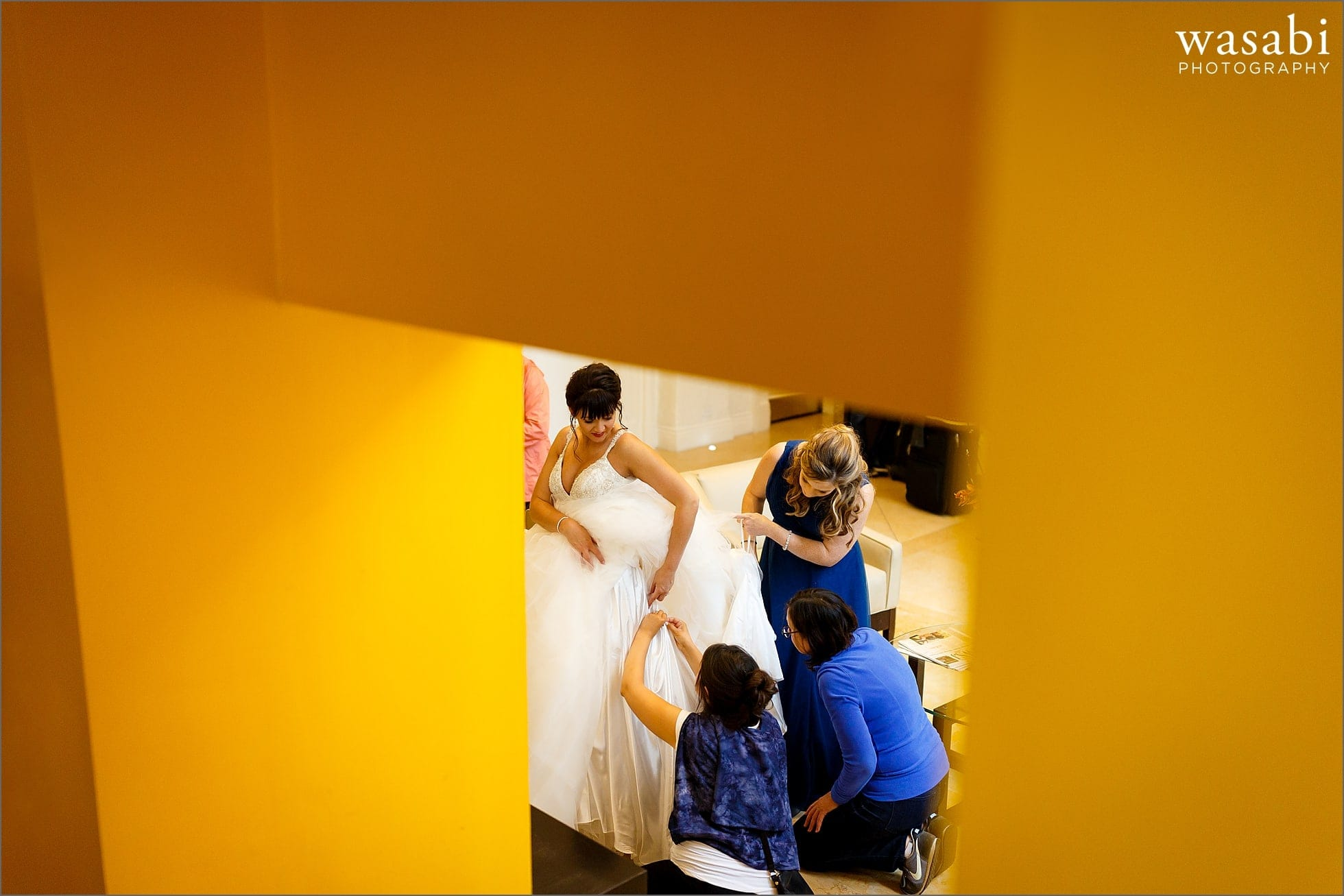 bridesmaids help bustle wedding dress in lobby of Rafaello Hotel in Chicago