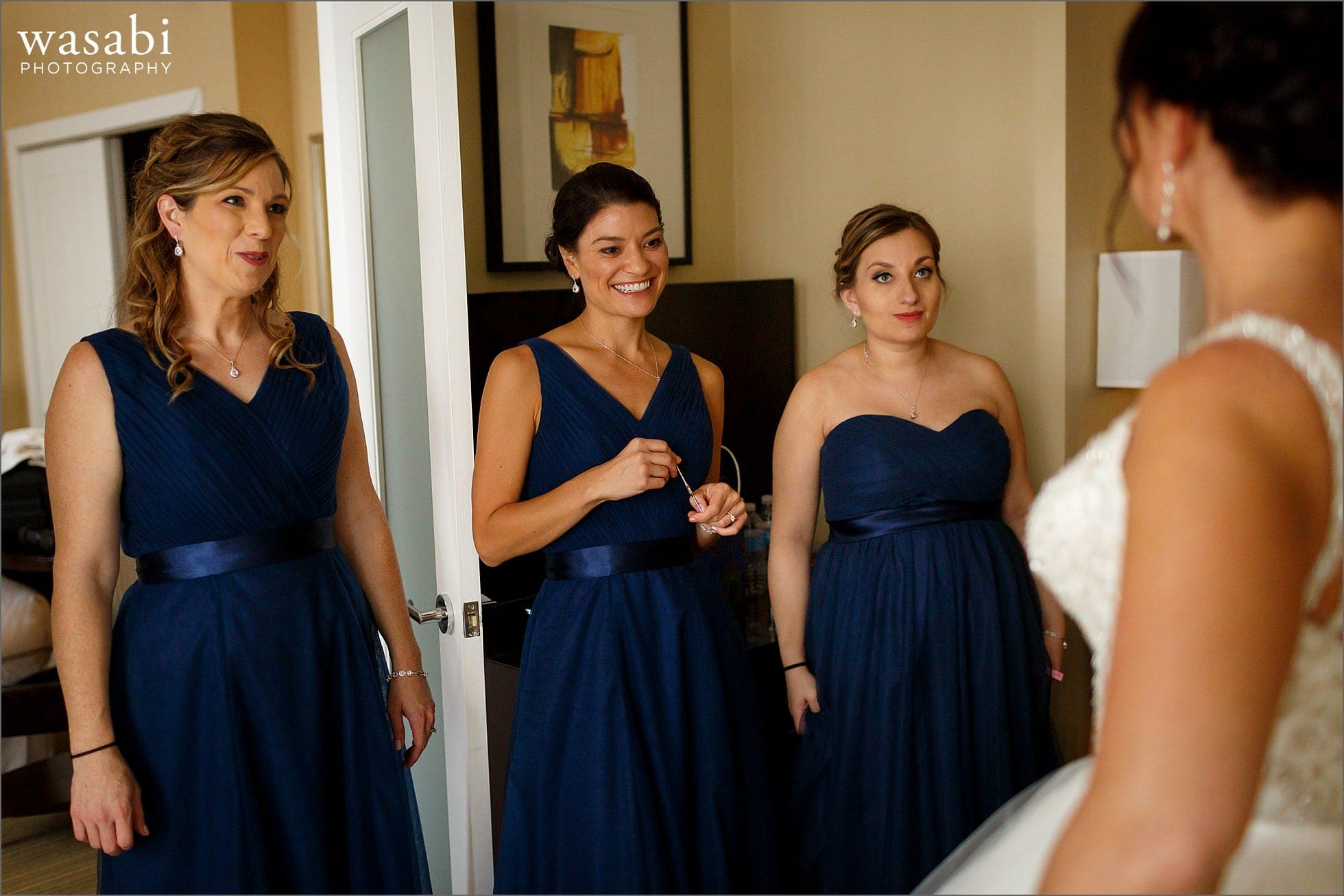 bridesmaids react to seeing bride in wedding dress while getting ready for her wedding at Raffaello Hotel in Chicago