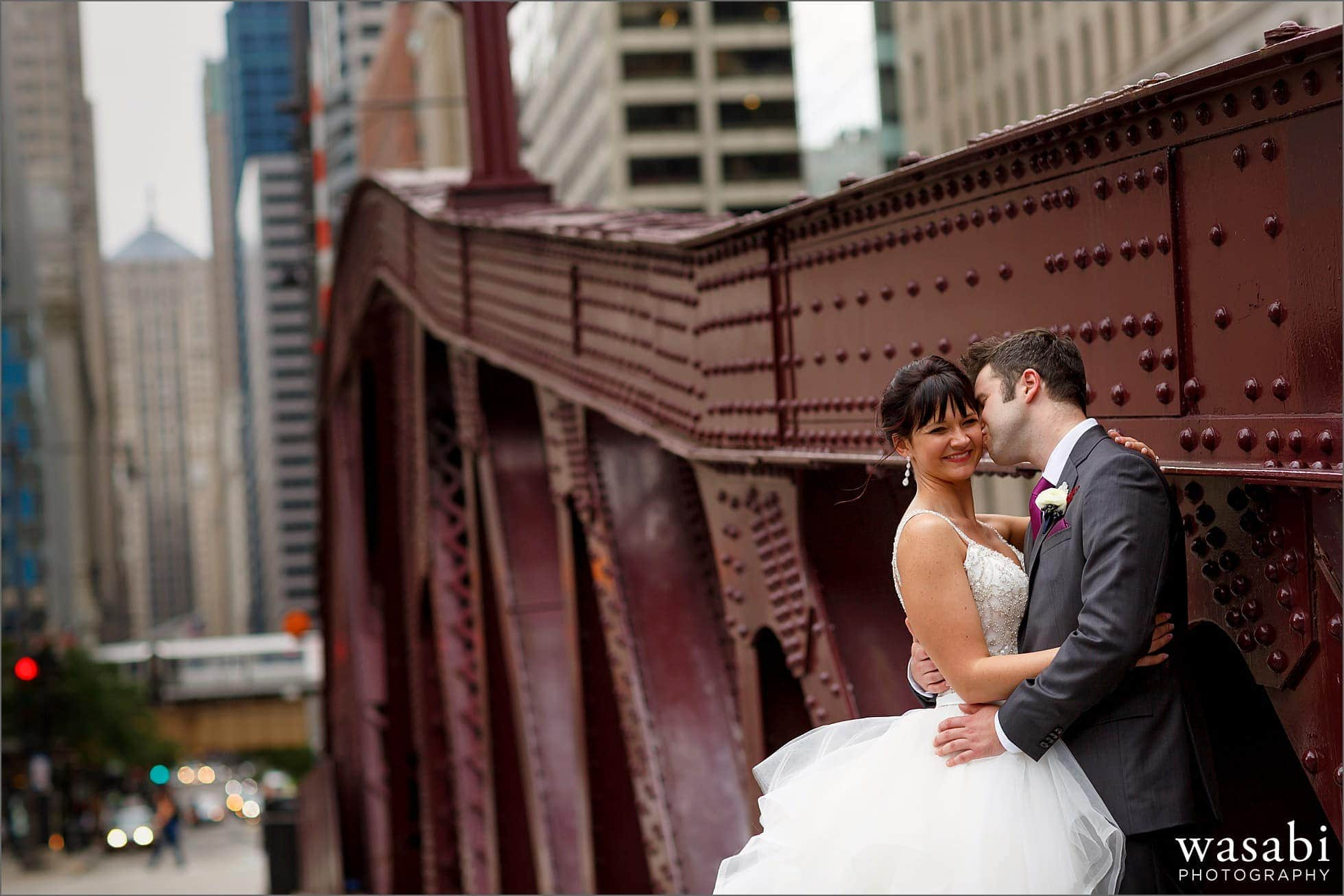 groom kisses bride on the cheek for wedding photo on LaSalle Street Bridge