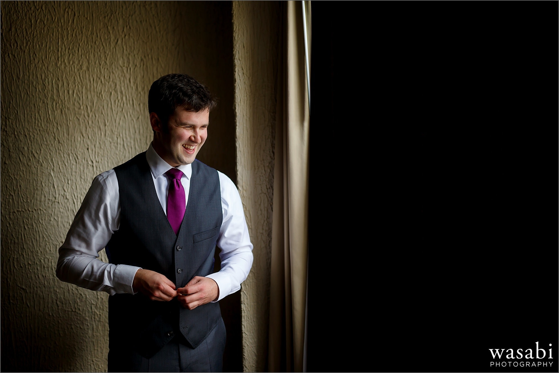 groom laughs while getting dressed in the window of his hotel room at Raffaello Hotel in Chicago