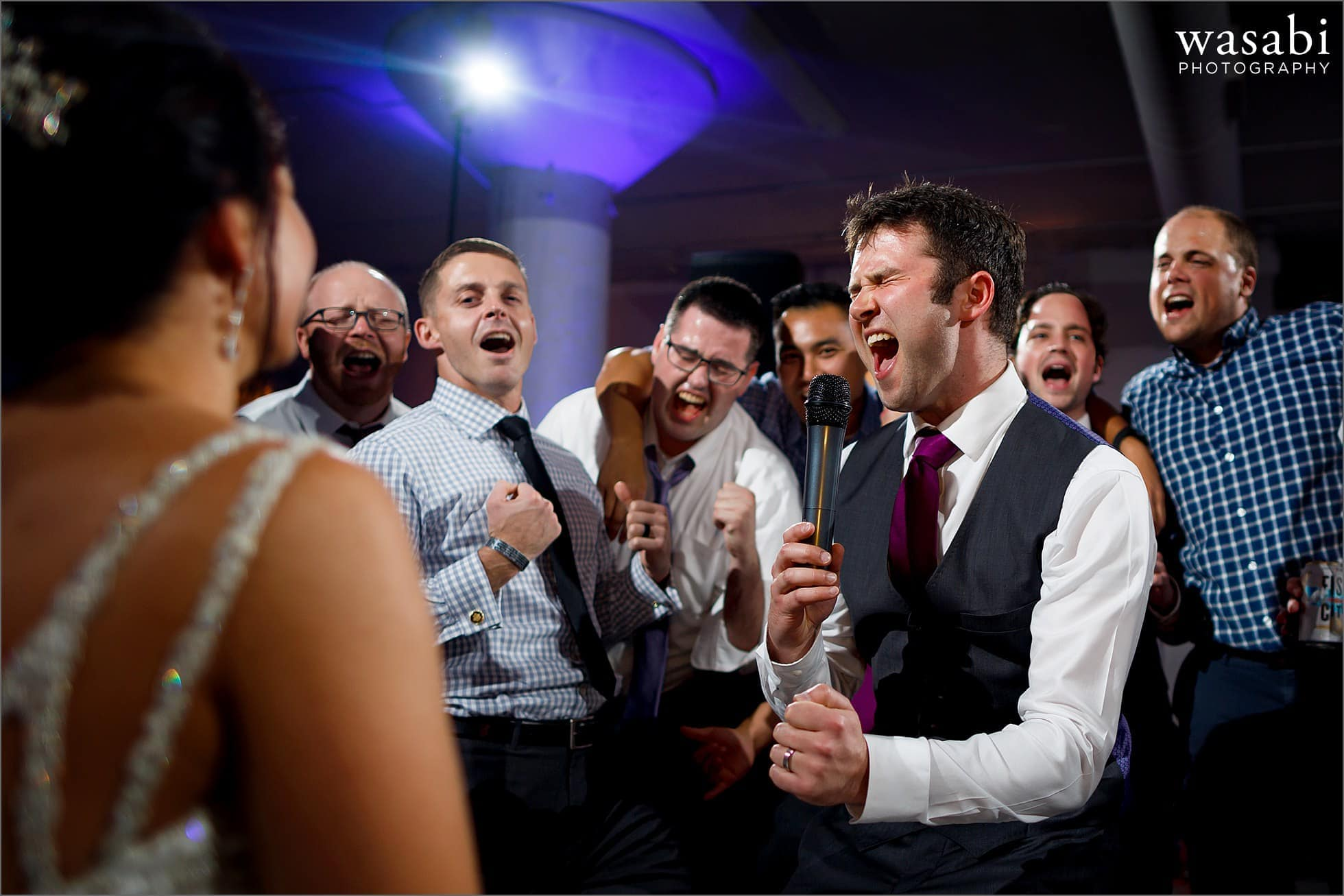 groom sings to his bride during wedding reception at Room 1520 in Chicago