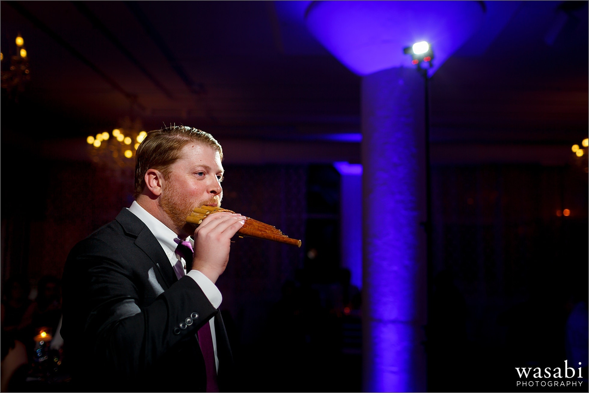 groomsmen plays pan flute during toast at wedding reception at Room 1520 in Chicago