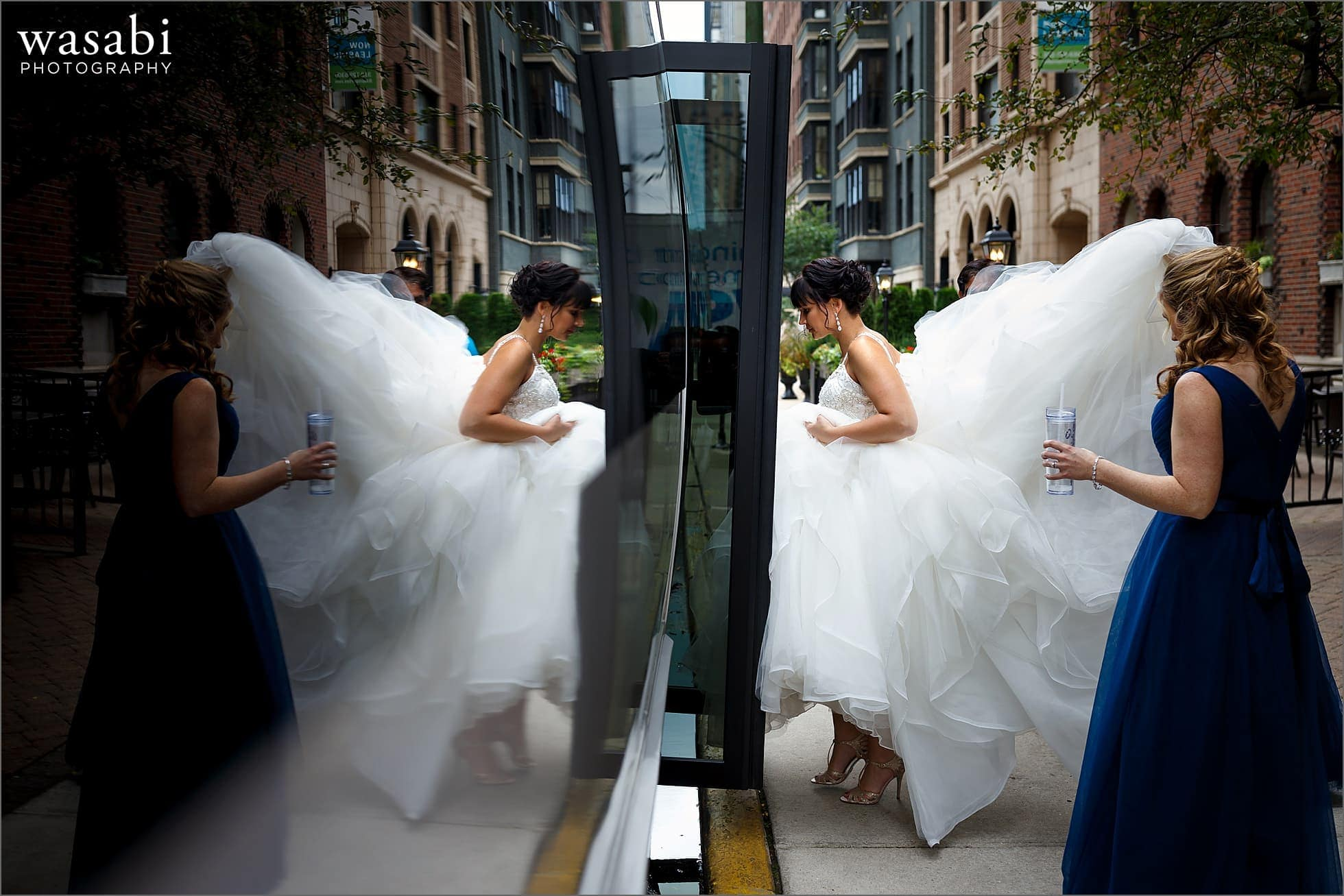 reflection picture of bridesmaid helping bride onto bus outside Rafaello Hotel in Chicago