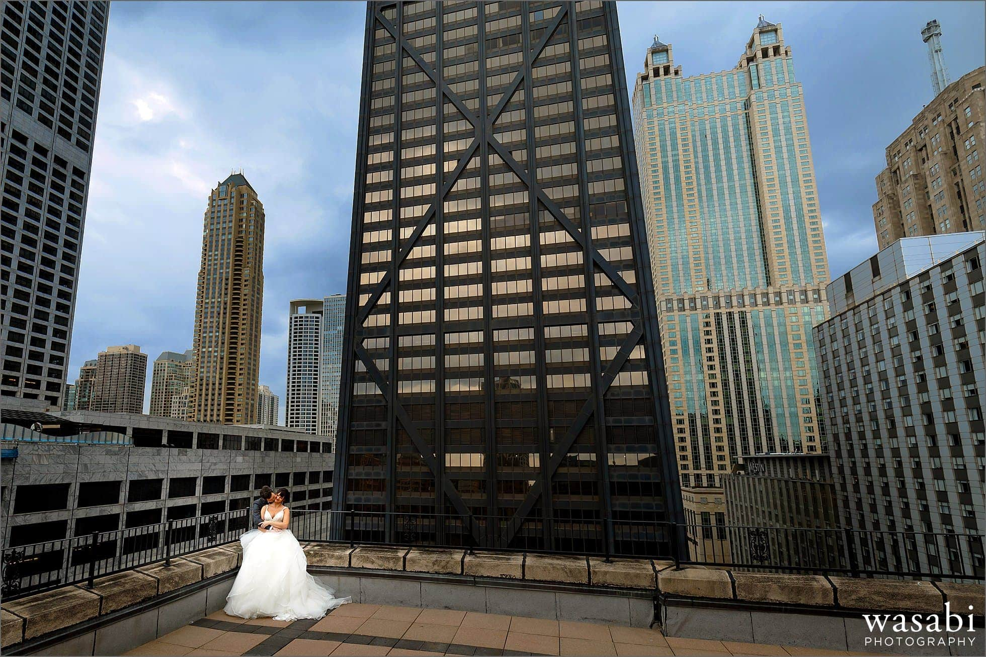 wide angle wedding portrait of bride and groom on the roof of Raffaello Hotel in Chicago with the Hancock building in the background