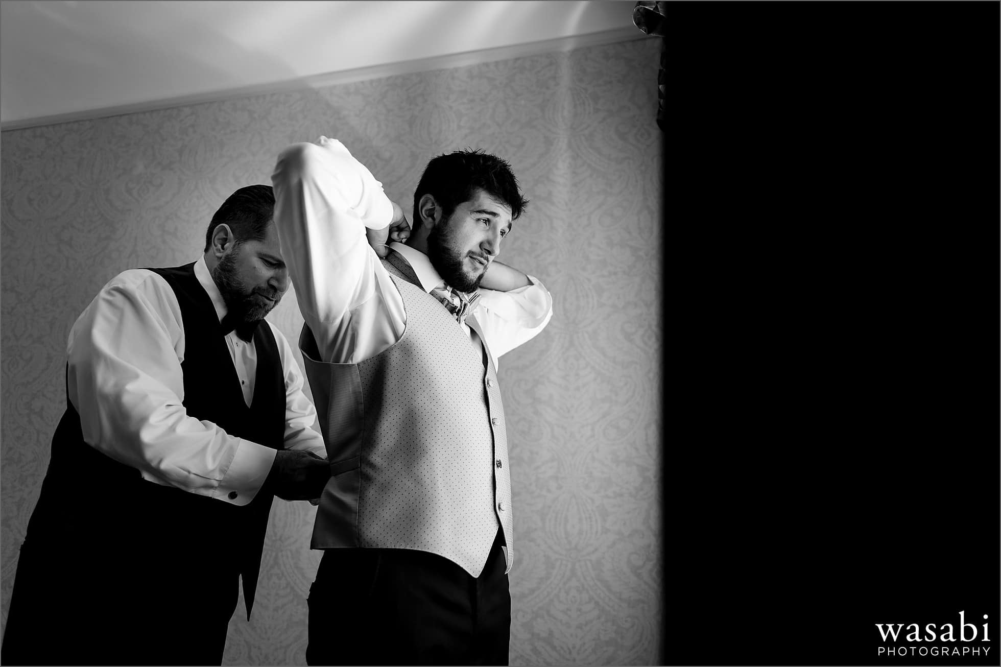 black and white groom and best man getting ready in hotel room with window light