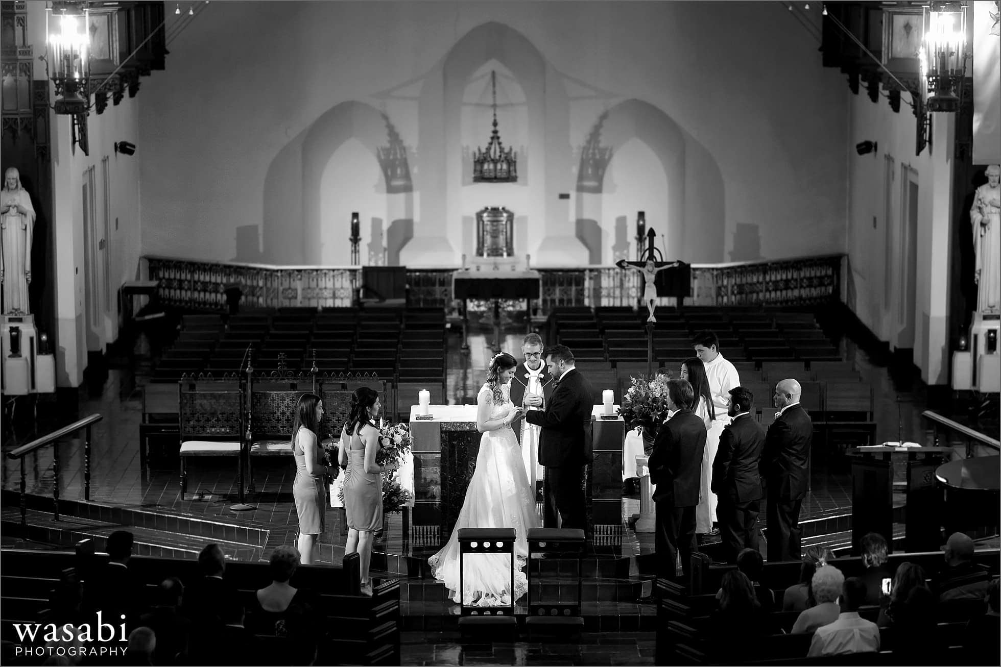 bride and groom exchange rings during wedding ceremony at St Luke Roman Catholic Church in River Forest
