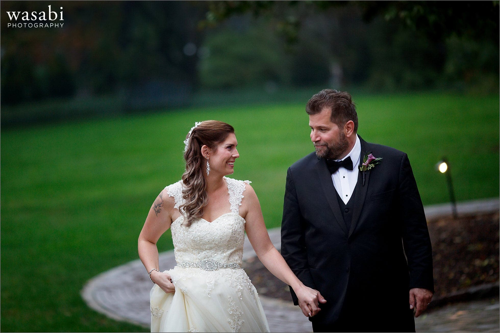 bride and groom go for walk on grounds at Cheney Mansion in Oak Park