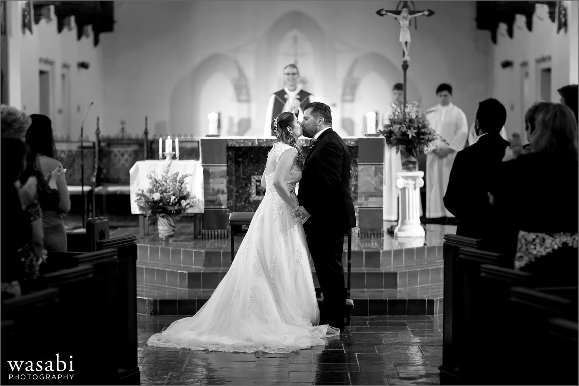 bride and groom kiss at the end of their wedding ceremony at St Luke Roman Catholic Church in River Forest