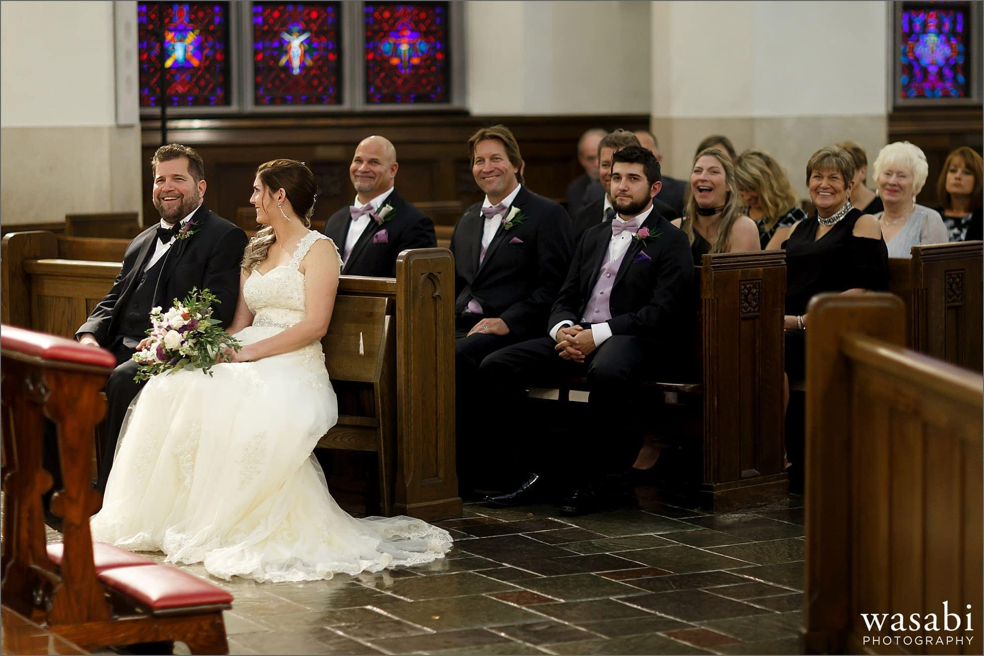 bride and groom laugh during wedding ceremony at St Luke Roman Catholic Church in River Forest