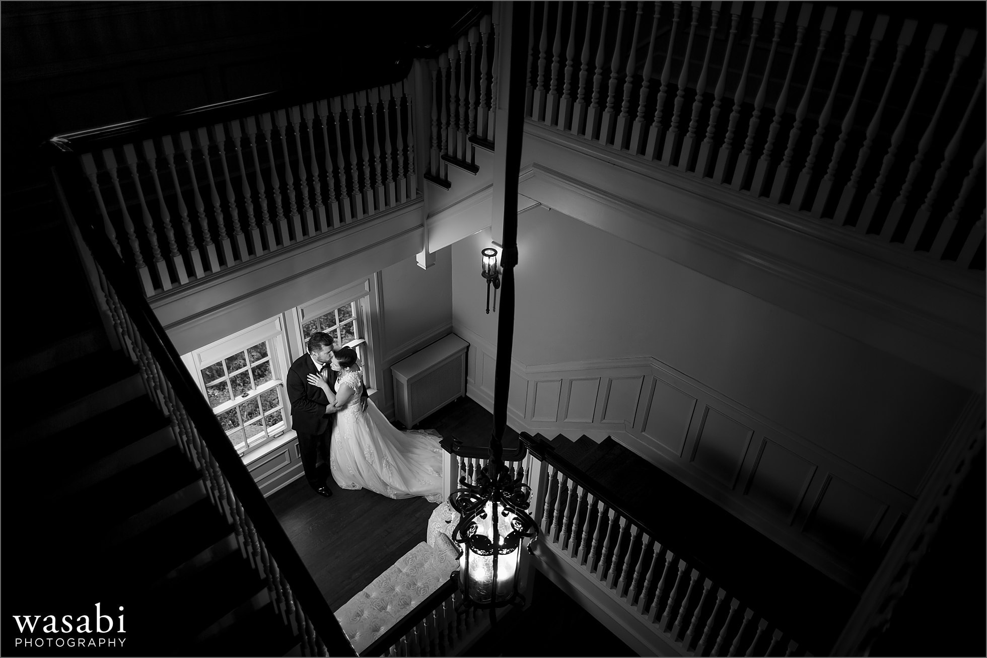 bride and groom pose for a wedding portrait on the staircase at Cheney Mansion in Oak Park