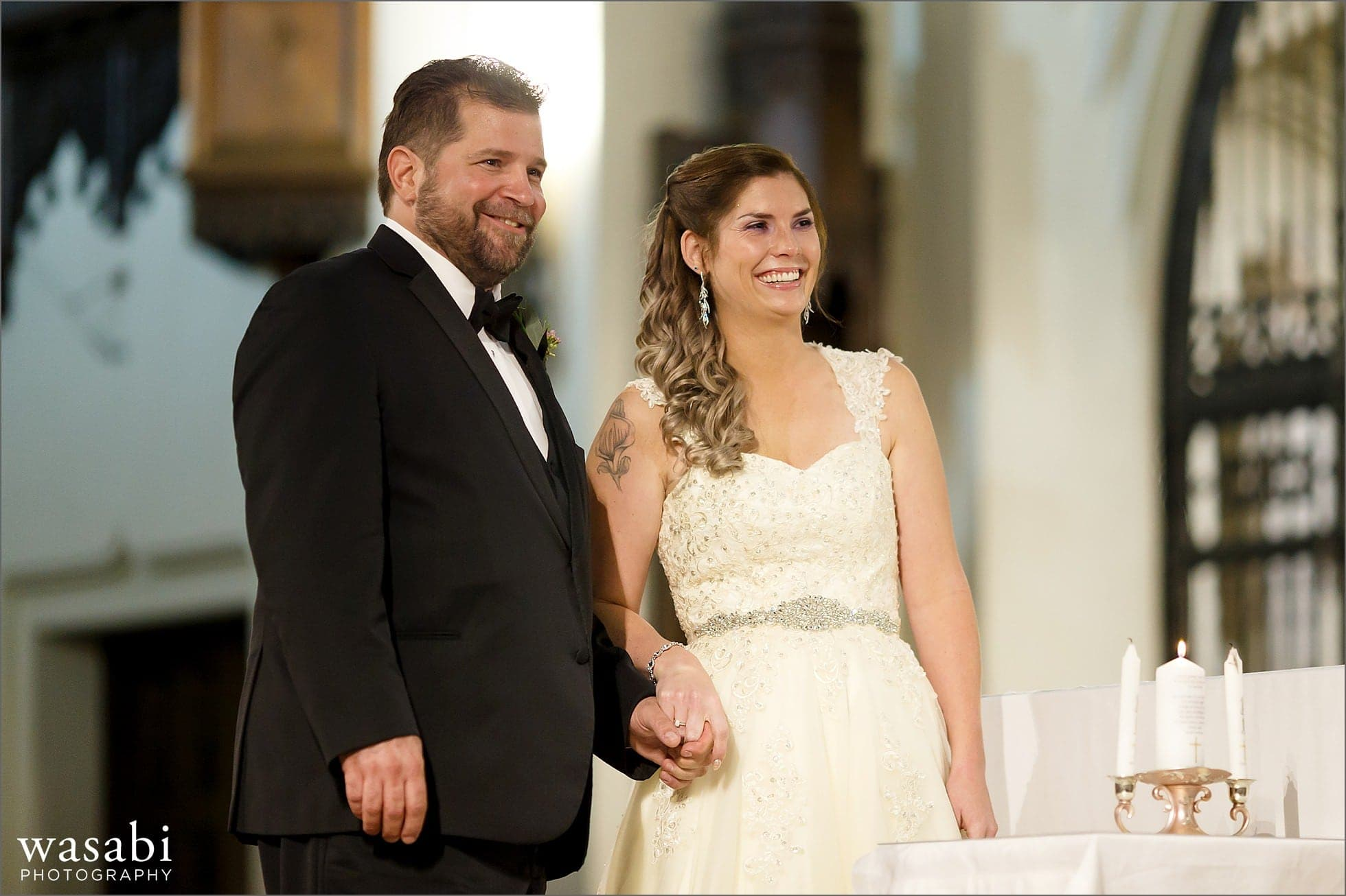 bride and groom smile while looking at their guests during wedding ceremony at St Luke Roman Catholic Church in River Forest