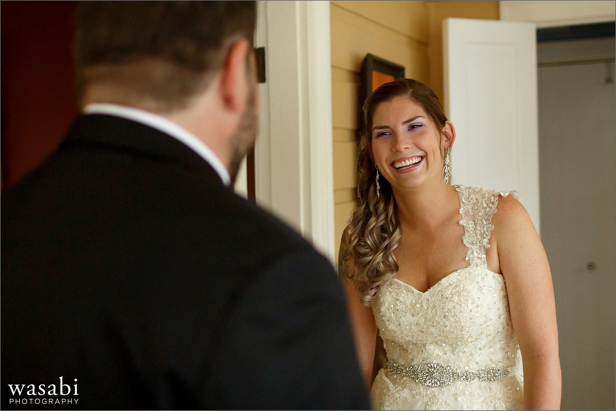 bride laughs during first look with groom in her home before the wedding