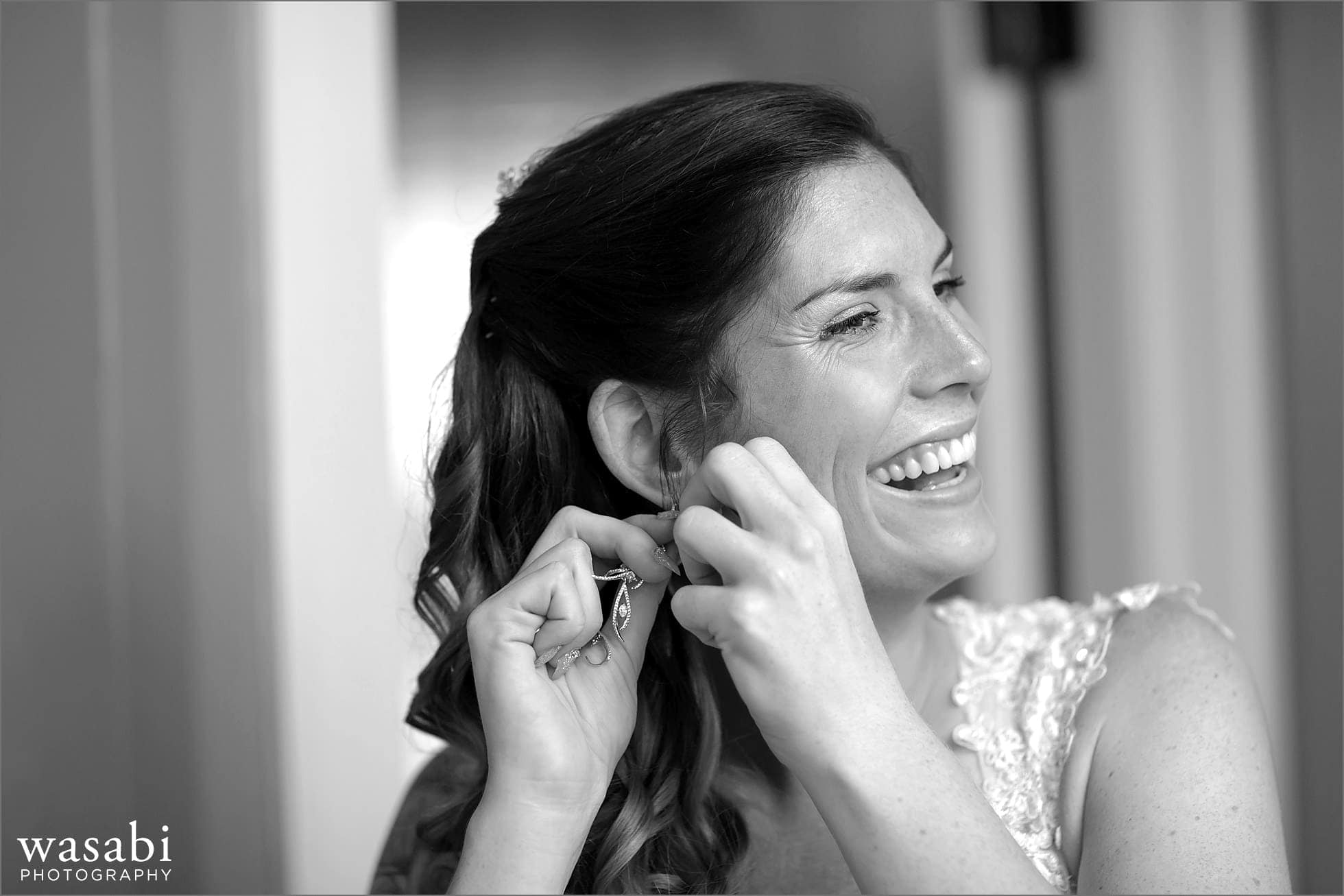 bride puts on earring while getting ready for her wedding