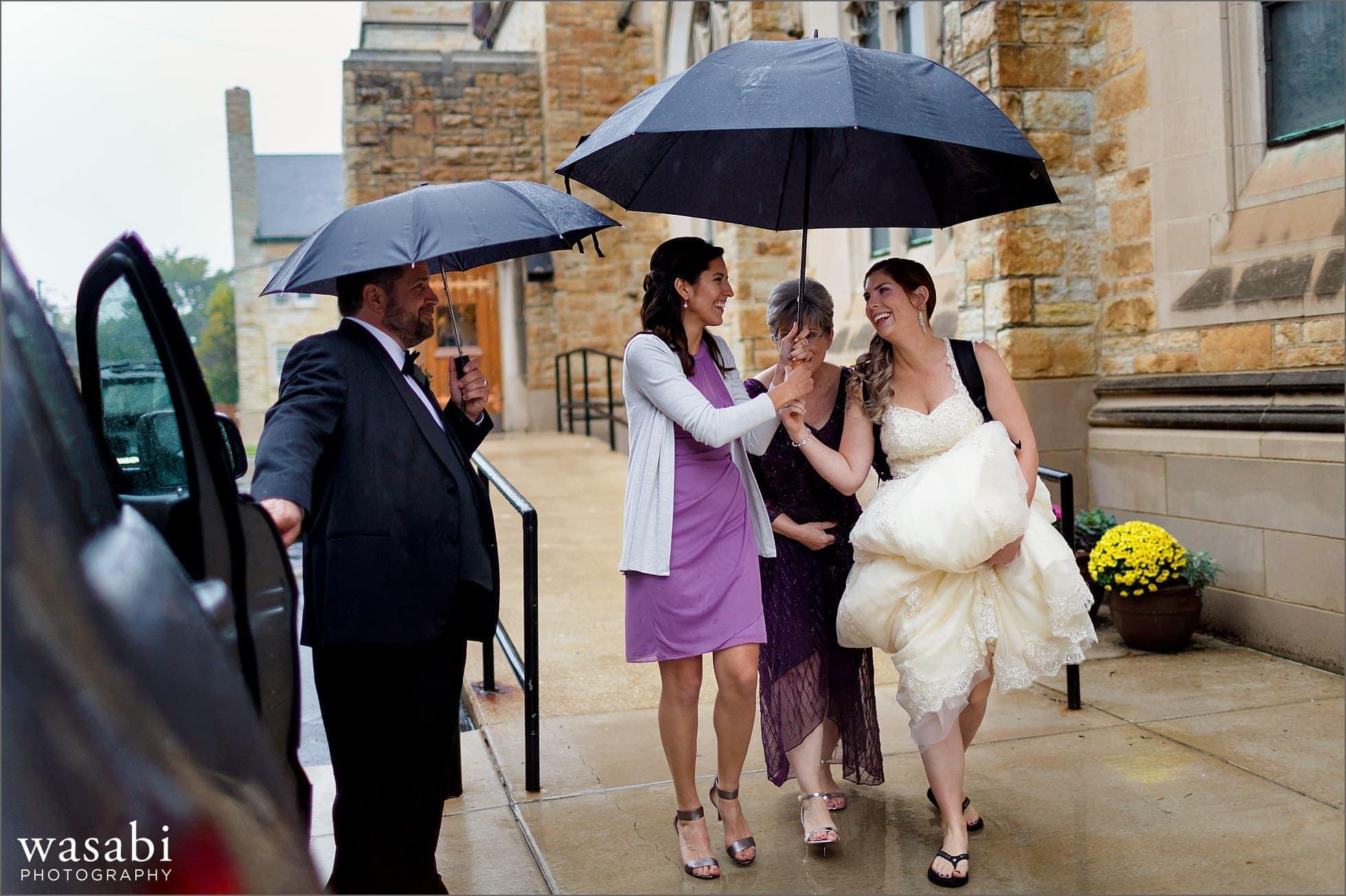 bride walks under umbrella to avoid rain while leaving ceremony at St Luke Roman Catholic Church in River Forest