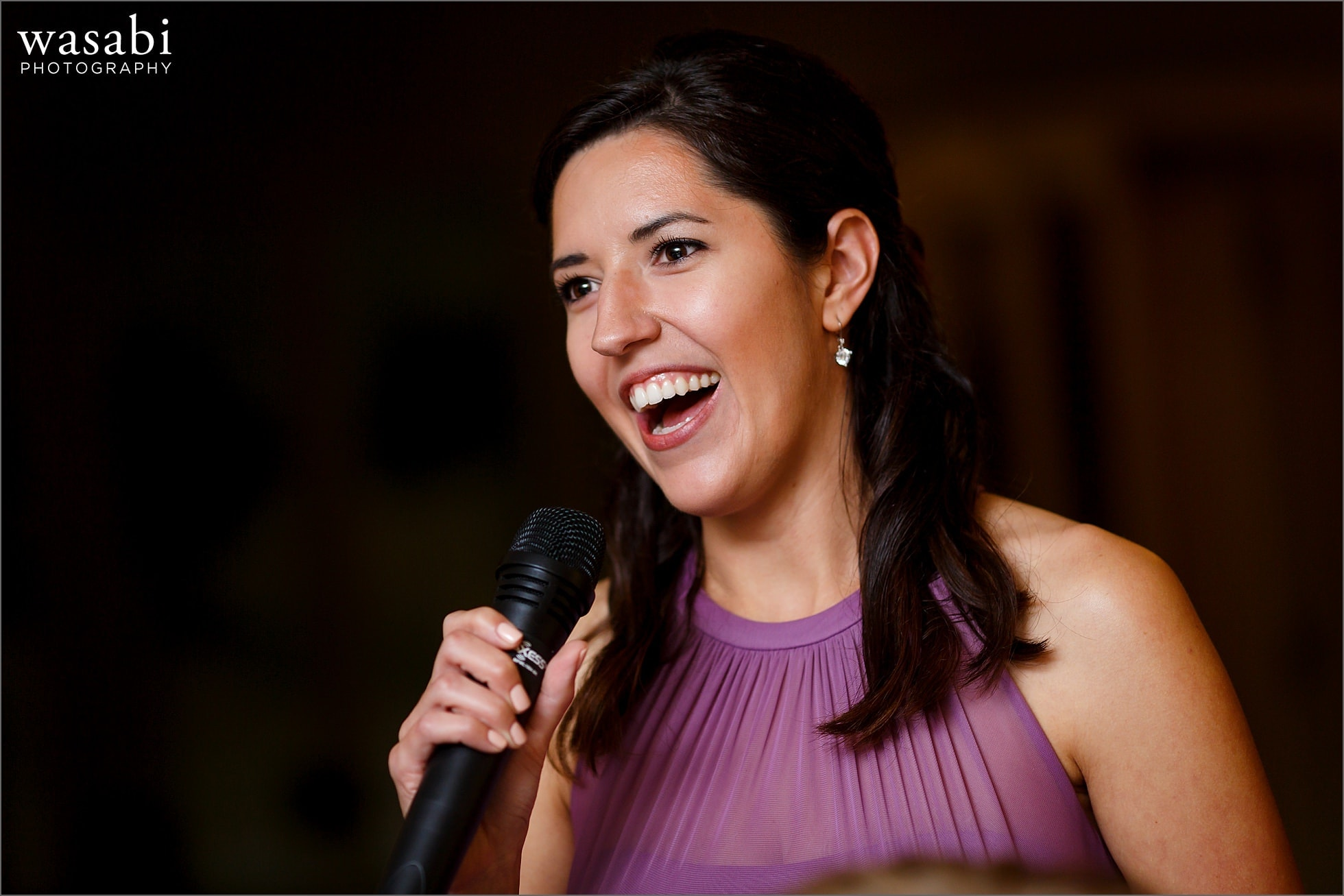bridesmaid smiles while giving toast during wedding reception at Cheney Mansion in Oak Park
