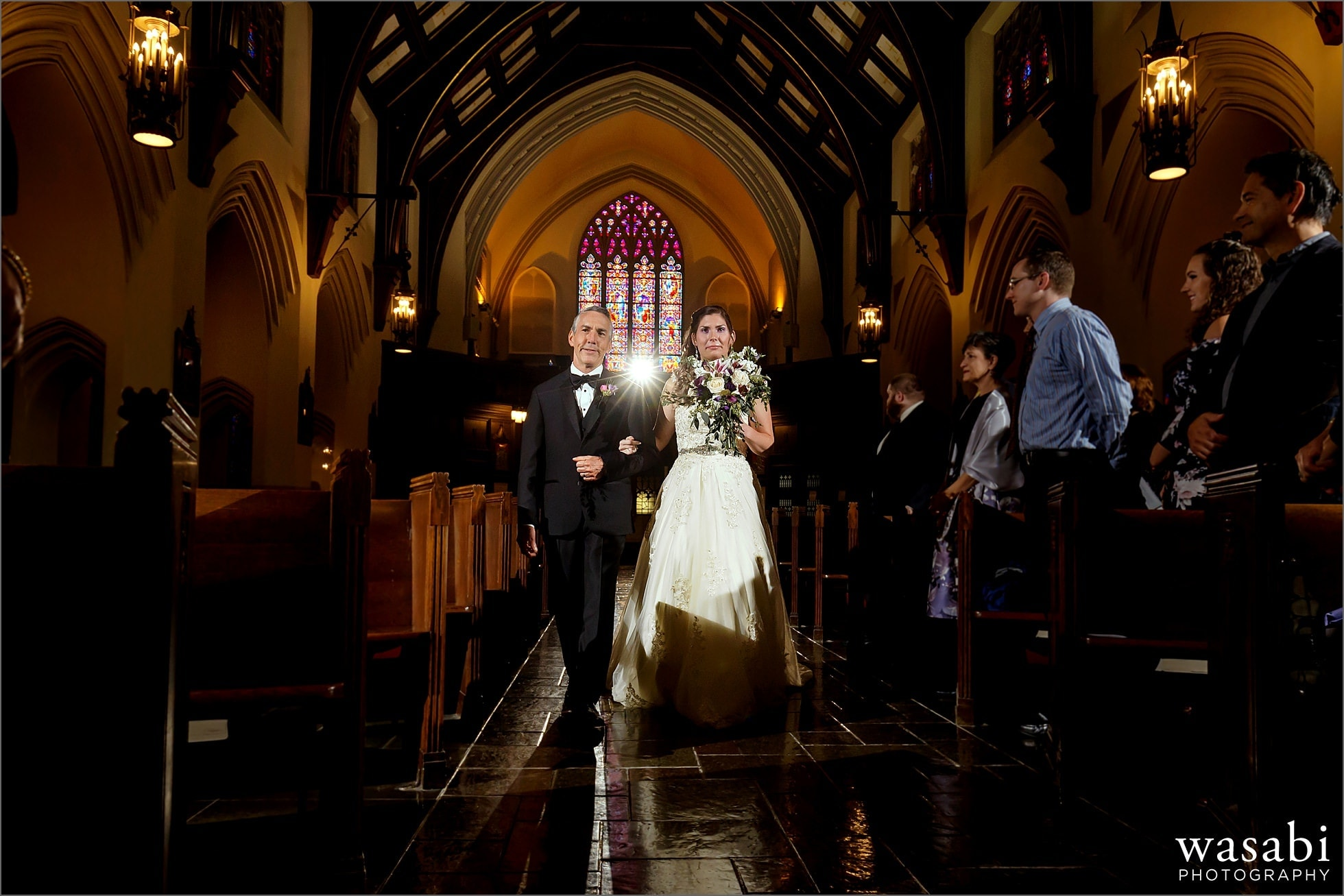 dramatic light off camera flash photo of bride walking down the aisle with her father at St Luke Roman Catholic Church in River Forest