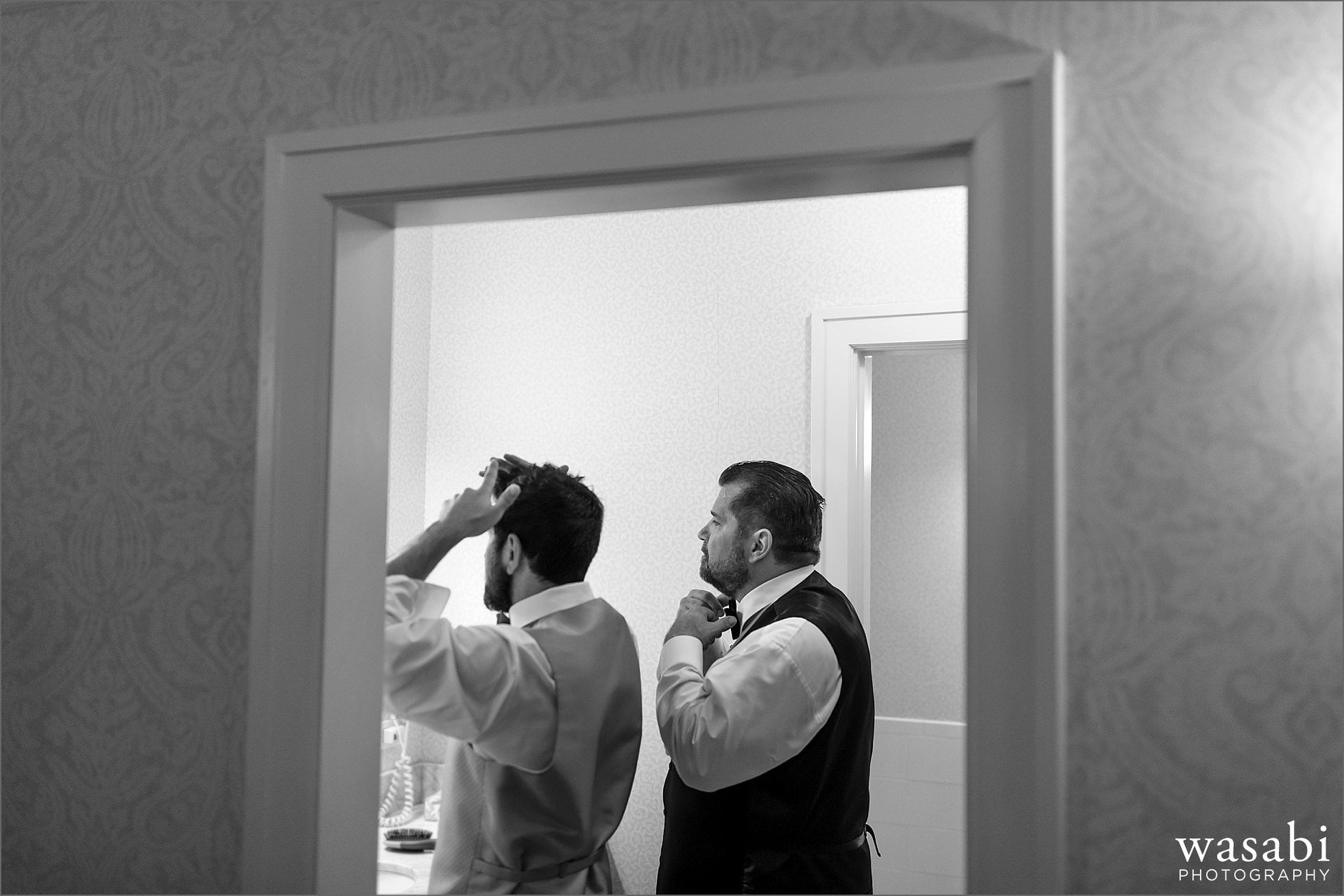 groom and best man do hair in bathroom while getting ready for wedding