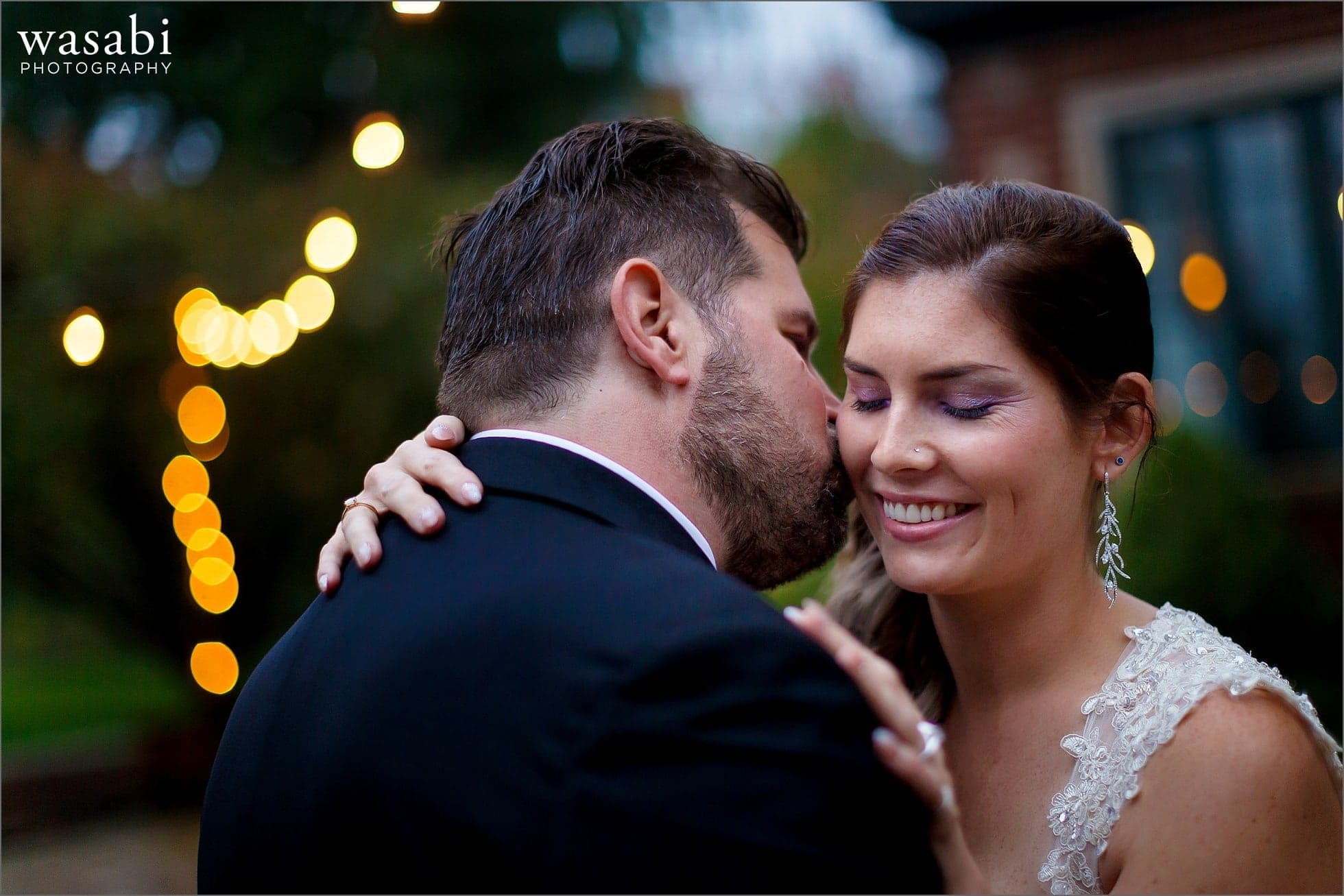 groom kisses bride on cheek during wedding portraits at Cheney Mansion at Oak Park