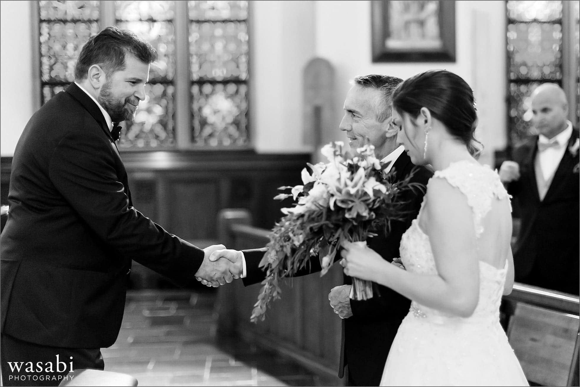 groom shakes hands with father of the bride during wedding ceremony at St Luke Roman Catholic Church in River Forest