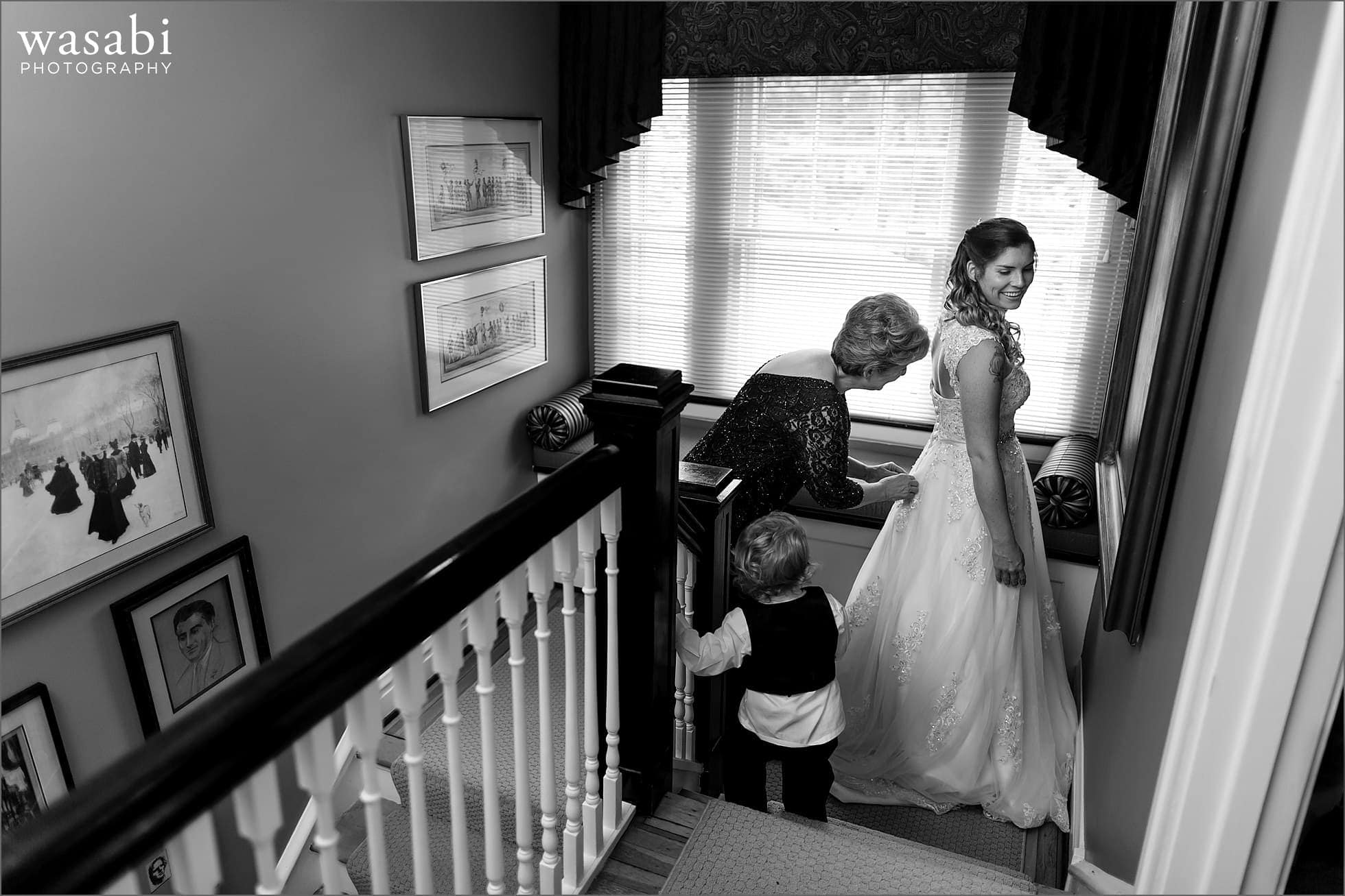 mother of bride helps with dress while getting ready at home