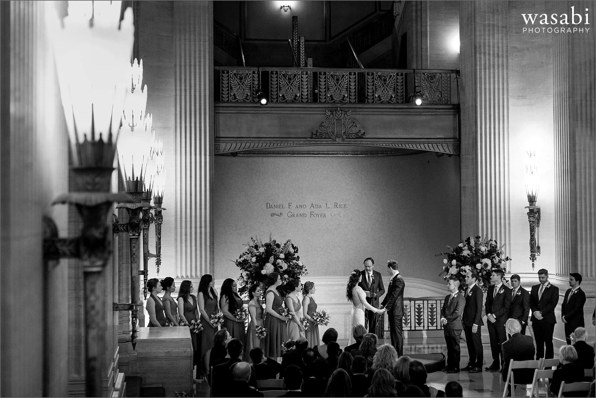 bride and groom hold hands during wedding ceremony at Lyric Opera House Chicago wedding in Daniel F. and Ada L. Rice Grand Foyer
