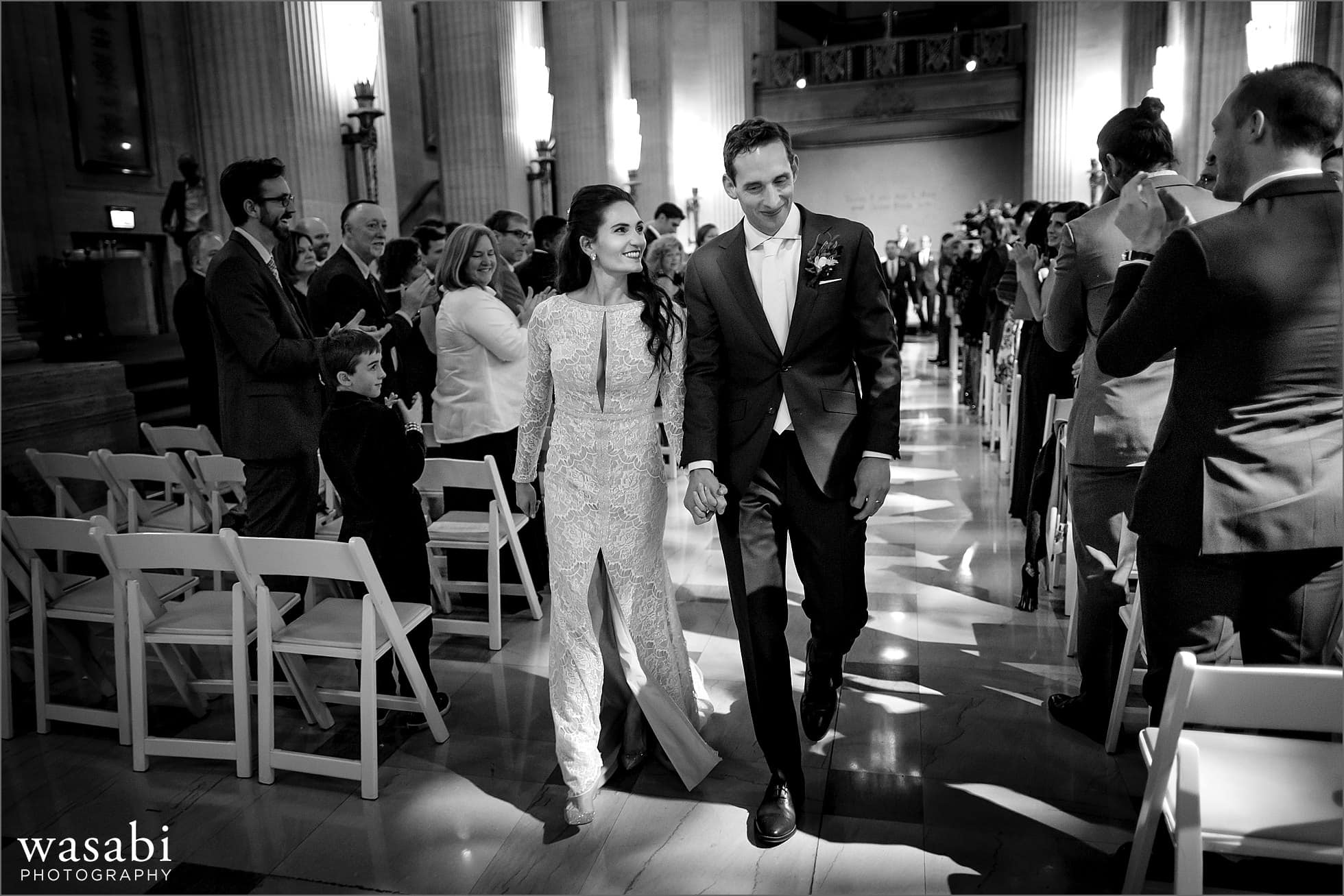 bride and groom hold hands walking back down aisle after getting wedding ceremony at Lyric Opera House Chicago wedding in Daniel F. and Ada L. Rice Grand Foyer