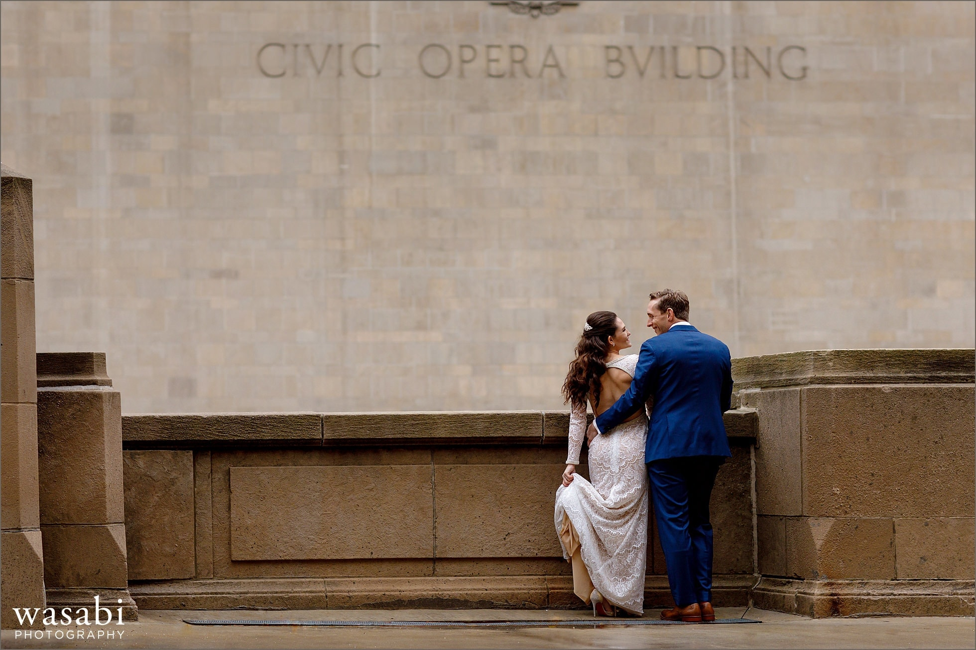 bride and groom pose for portrait with Civic Opera Building in the background in downtown Chicago