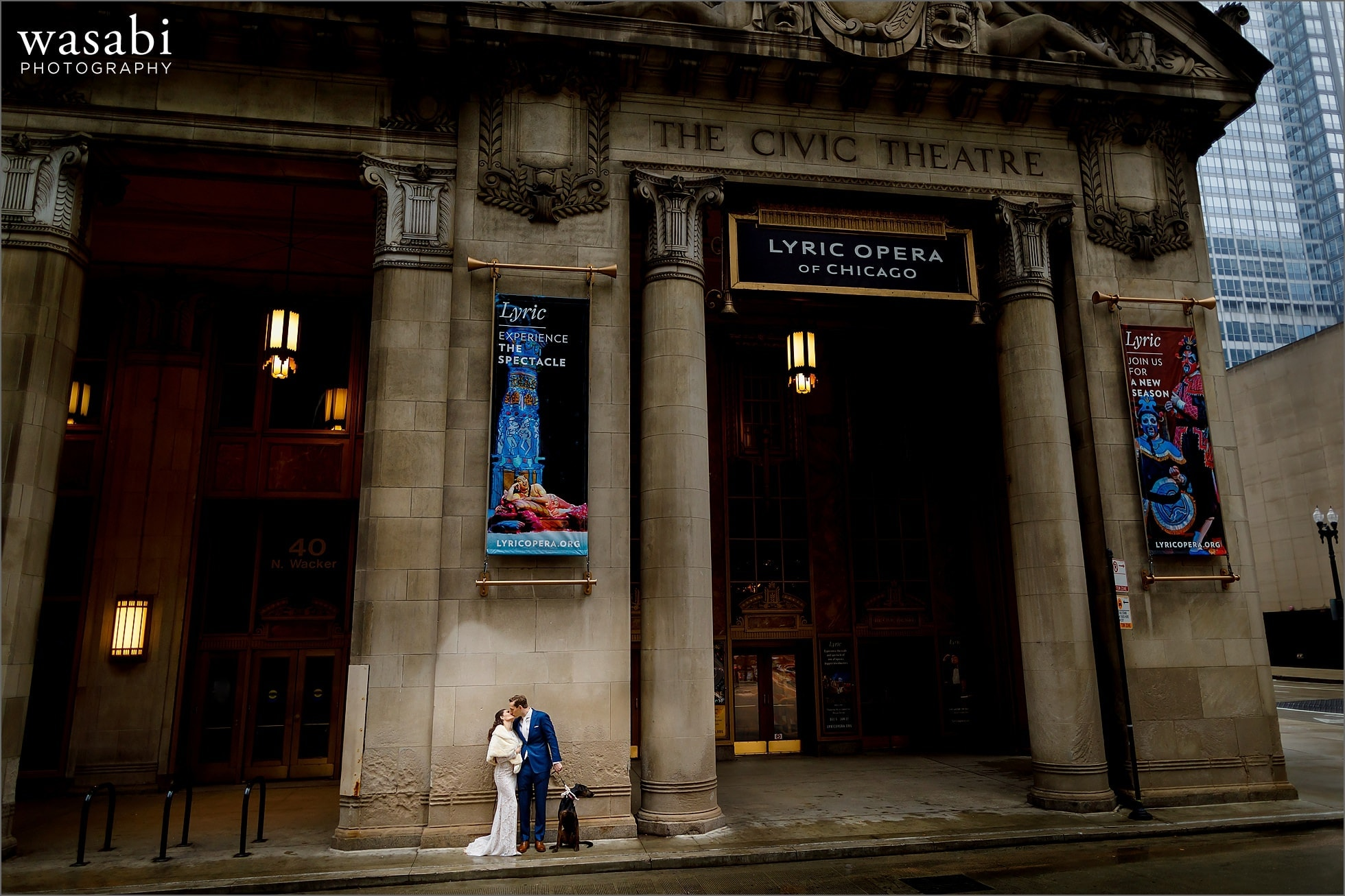 bride and groom pose with their dog for portrait at The Civic Theatre before their Lyric Opera of Chicago building wedding