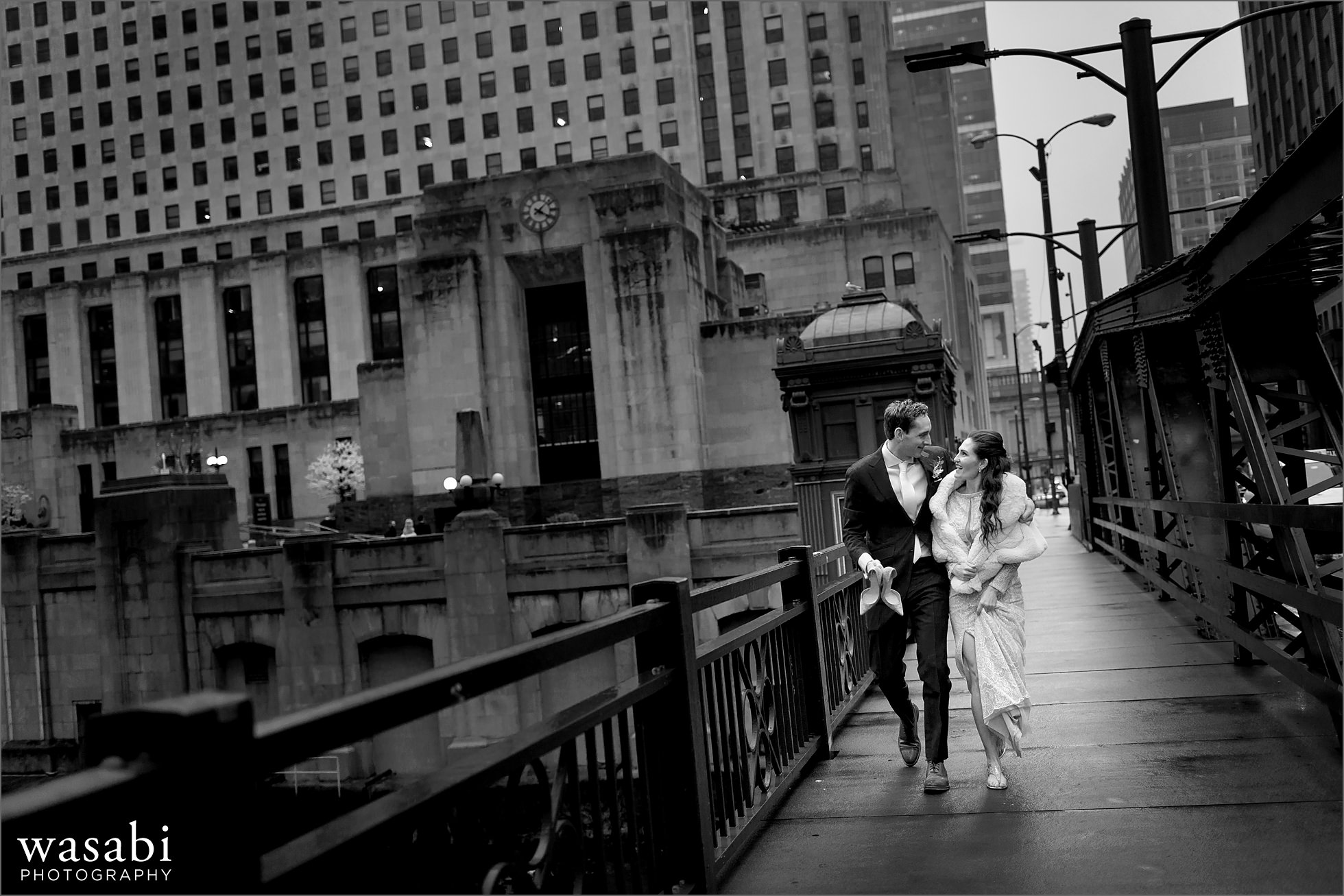bride and groom walk across Washington Street bridge before their Lyric Opera of Chicago wedding