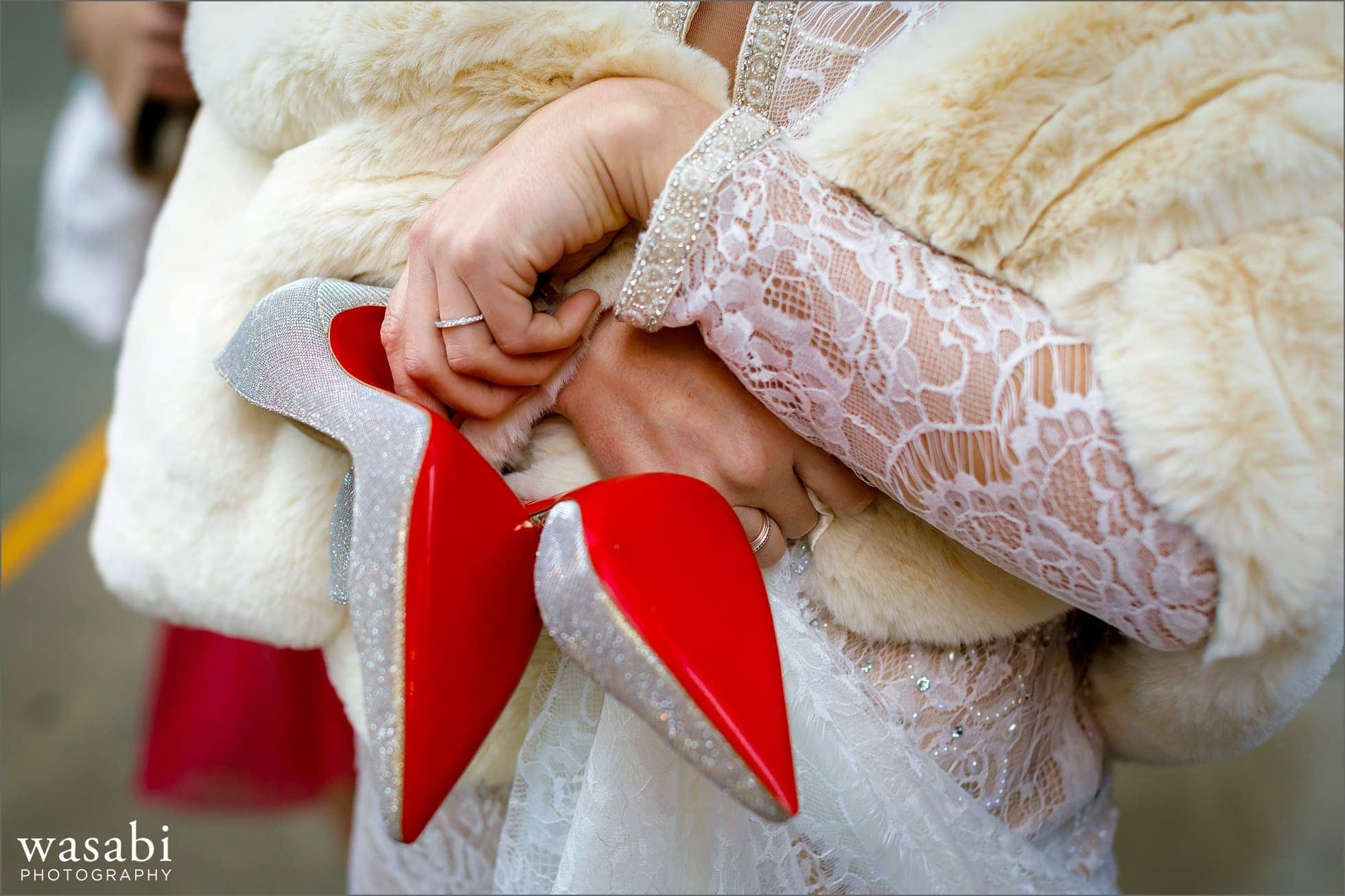 bride holds pair of Christian Louboutin red sole designer shoes on wedding day in Chicago