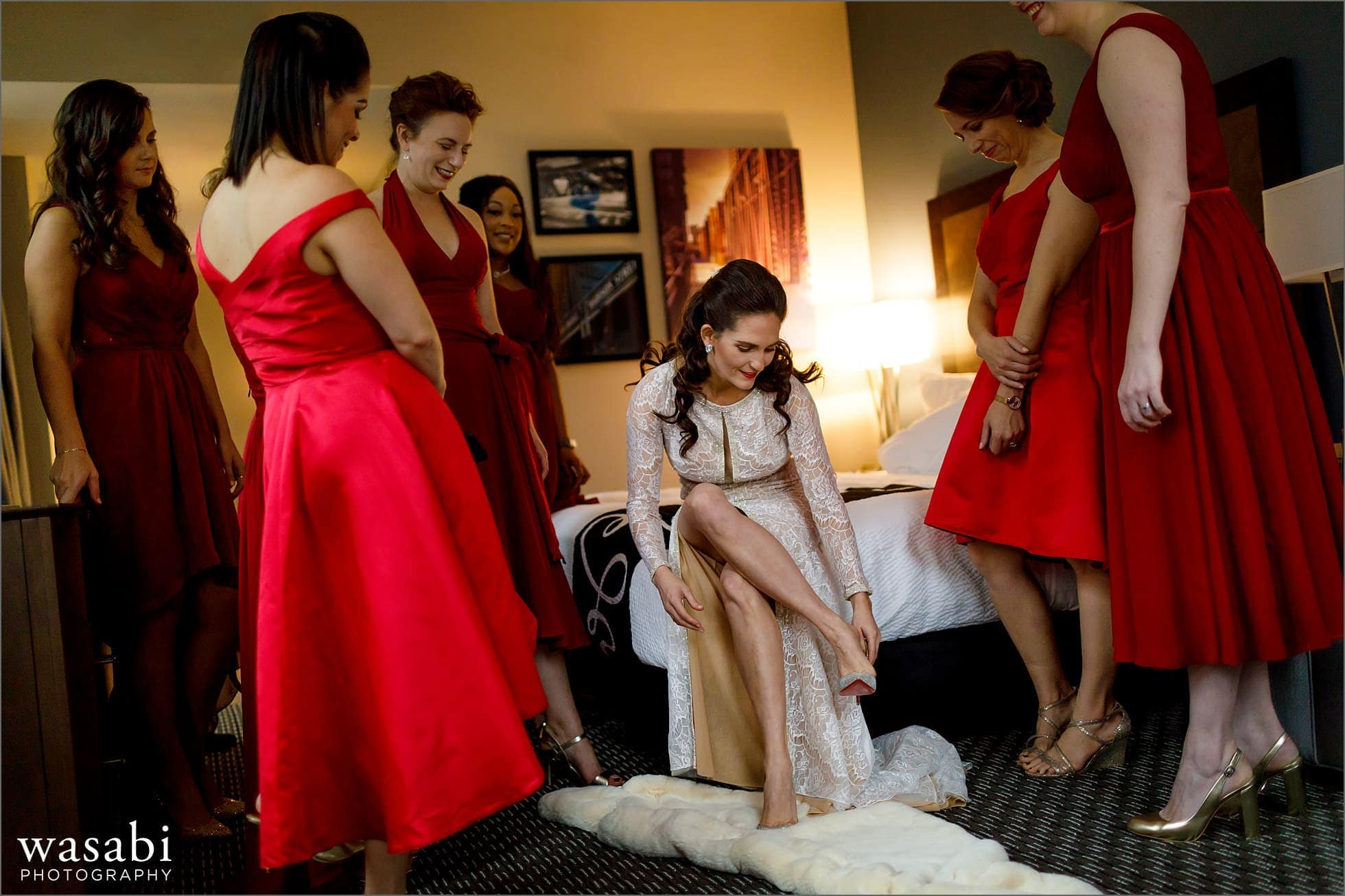 bride puts on shoes surrounded by bridesmaids while getting ready at La Quinta Inn in downtown Chicago for a wedding