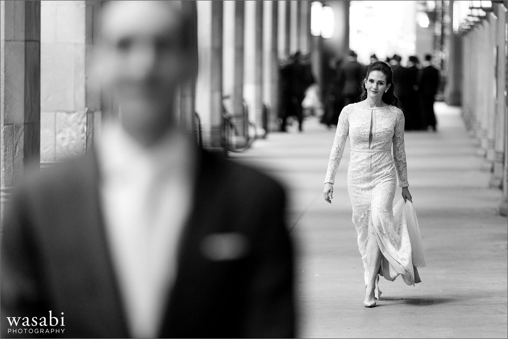bride walks toward groom during first look at Civic Opera House in Chicago before their wedding