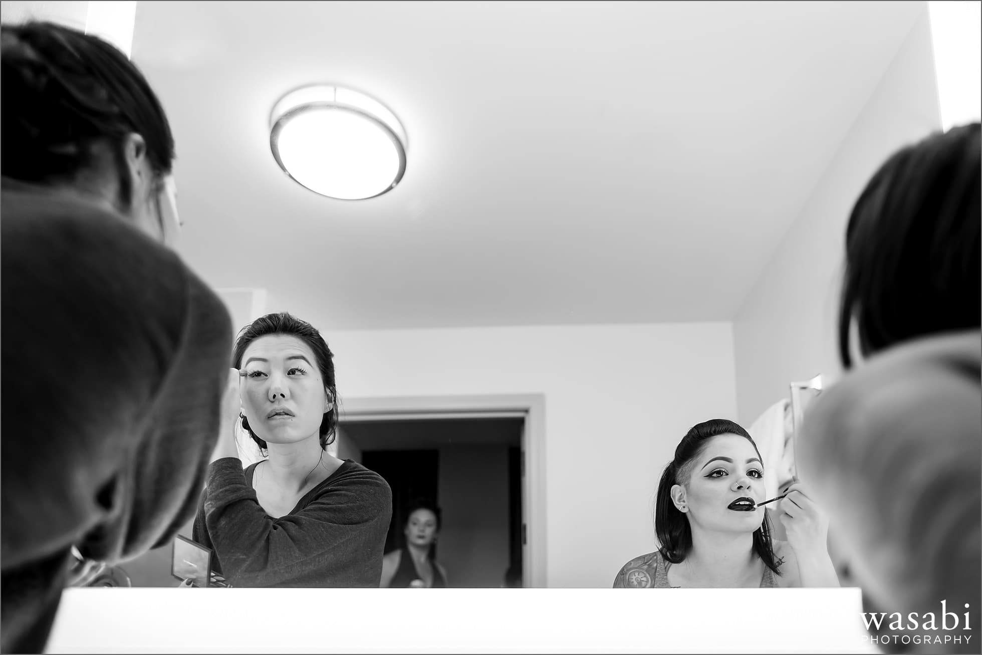 bridesmaids put on makeup in the bathroom mirror while getting ready at La Quinta Inn in downtown Chicago for a wedding