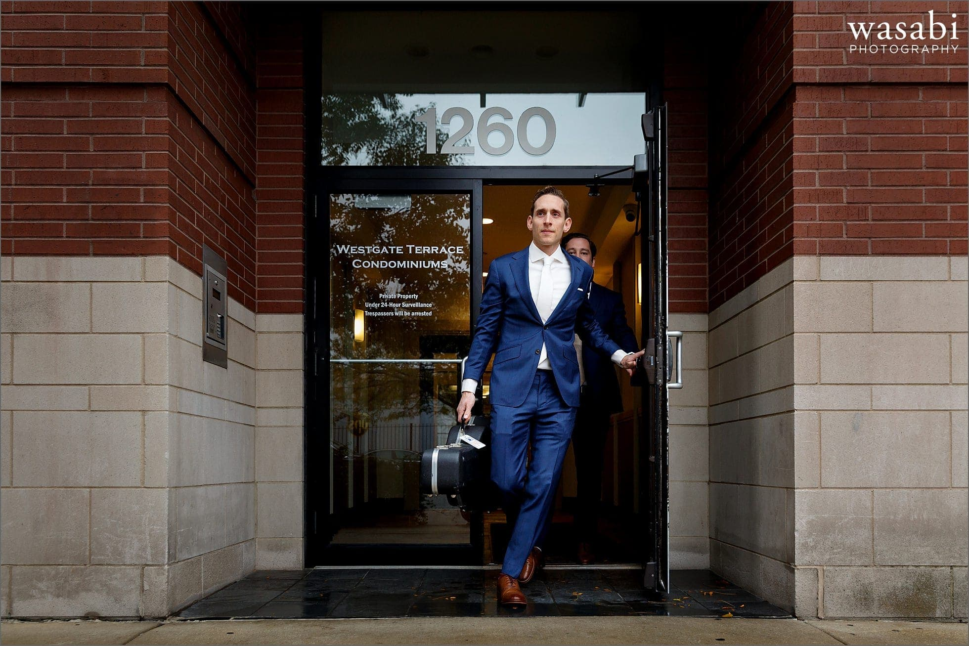 groom exits his condo building with guitar while going to wedding