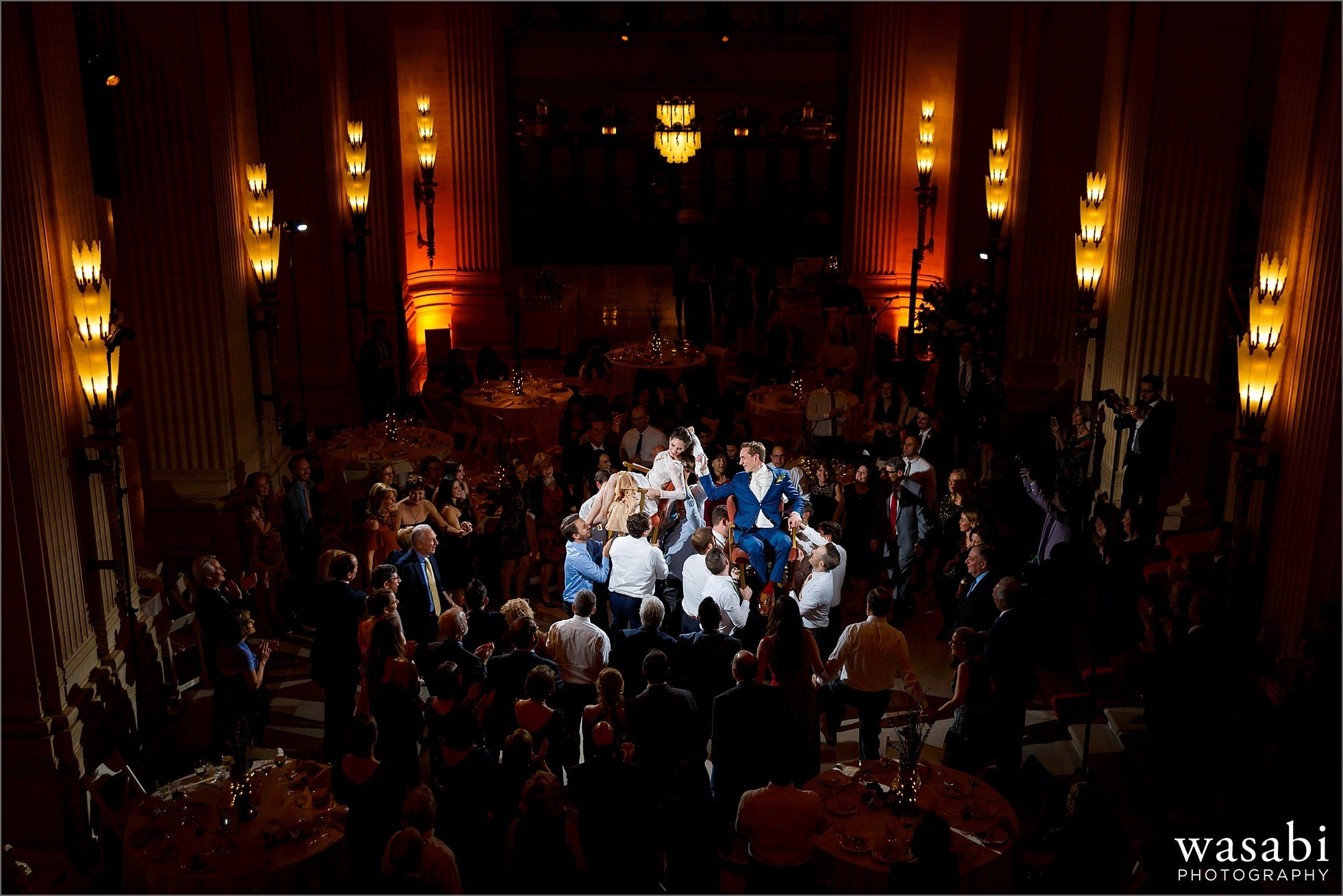 wide angle photo showing couple lifted up on chairs during the horah dance at Lyric Opera of Chicago wedding in Chicago