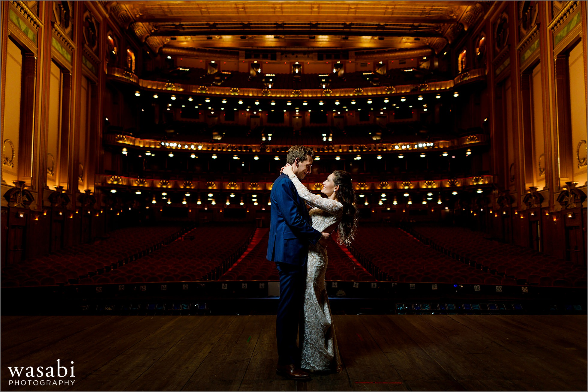 wide angle photos showing entire theatre while bride and groom pose for portrait on stage at Lyric Opera House Chicago wedding
