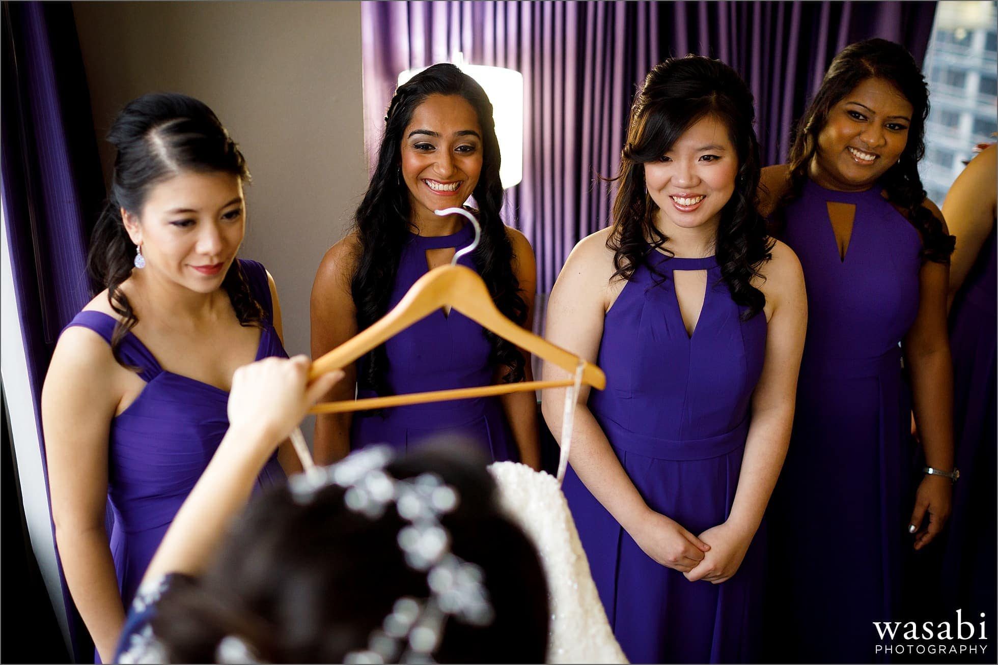 Bridesmaids watch while bride steps into wedding dress at Holiday Inn Chicago Mart Plaza River North