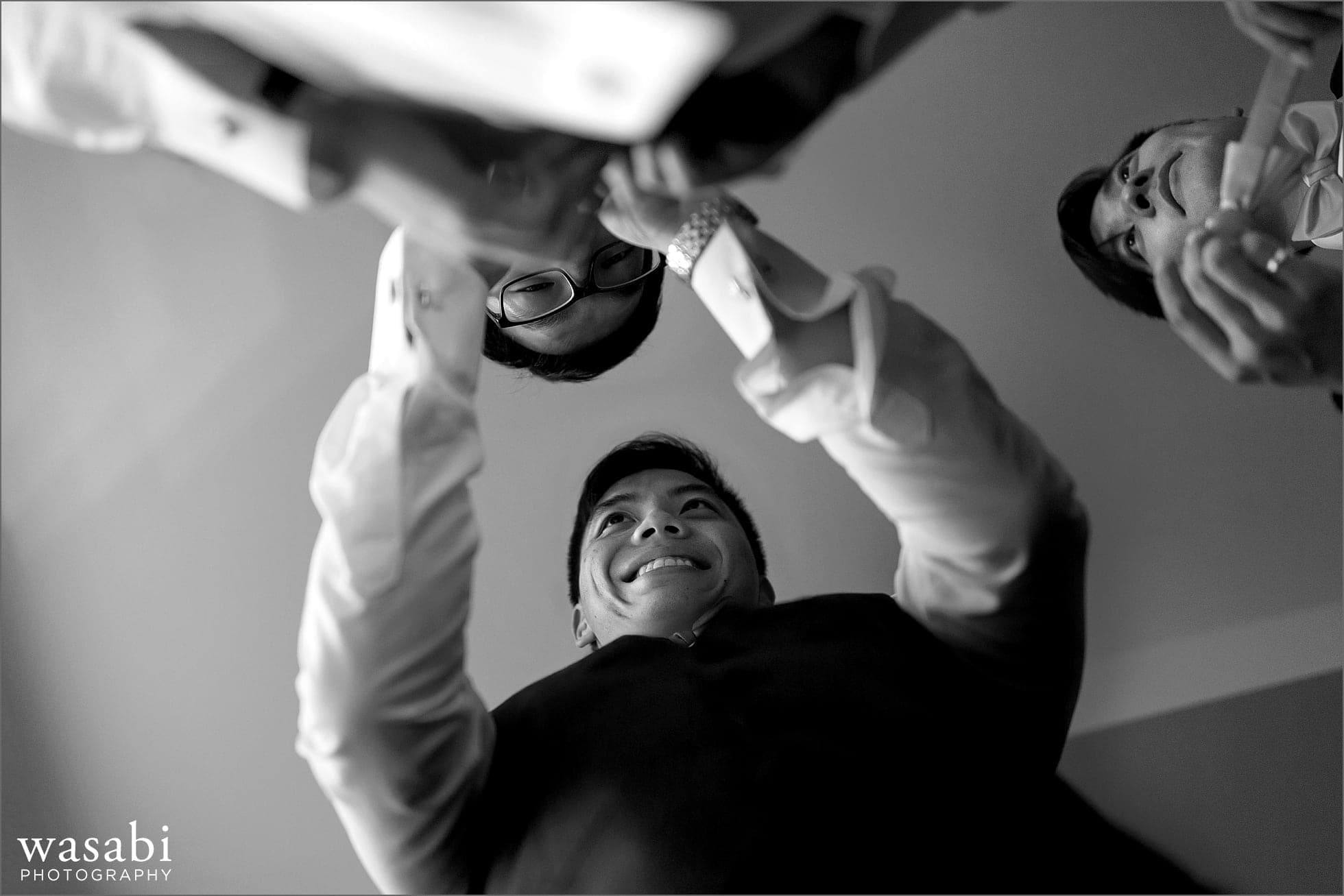 Unique angle of groom getting ready with groomsmen