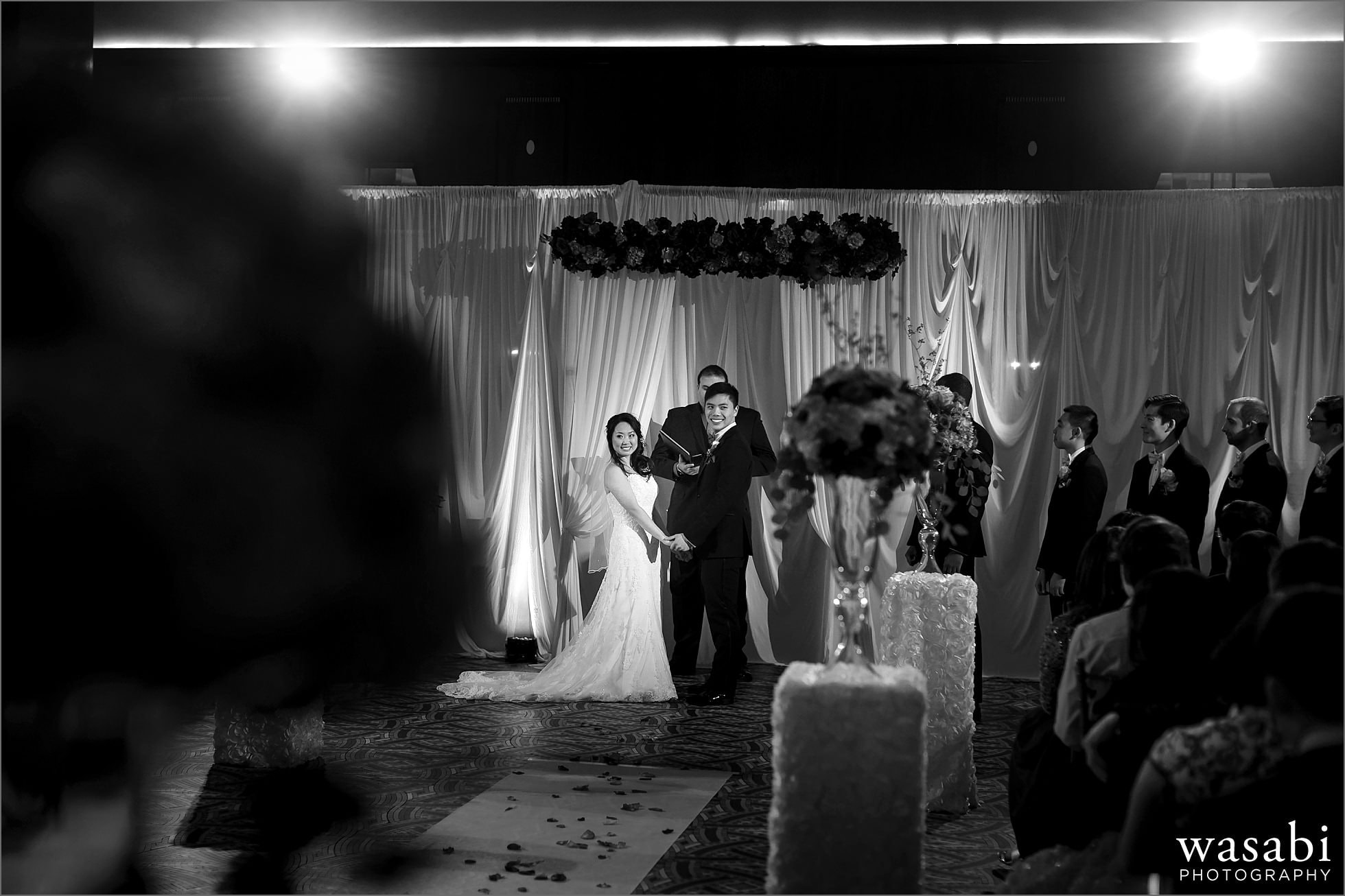 bride and groom look out toward their guests during ceremony at Montgomery Club wedding in Chicago