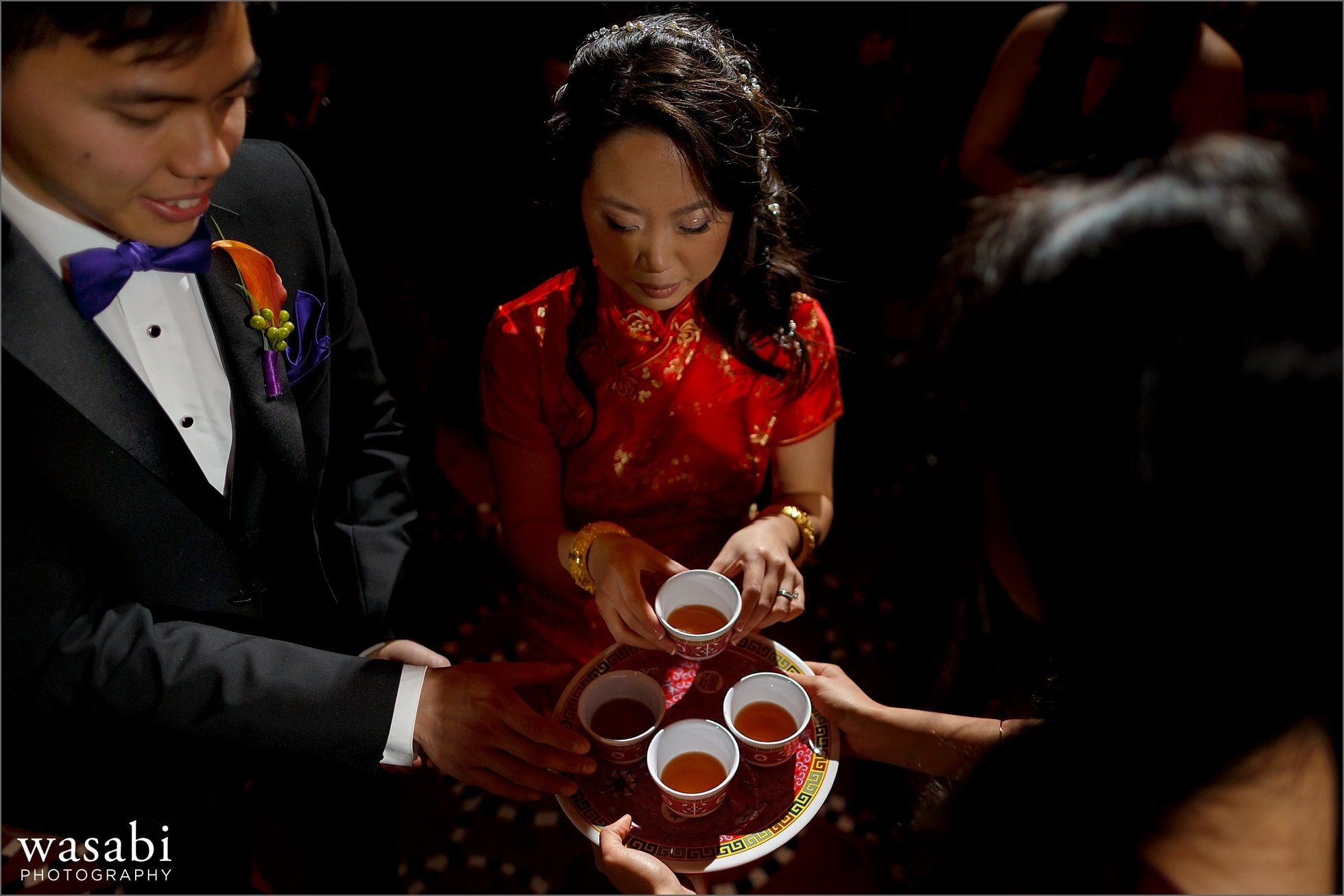 bride and groom pick up cups during Chinese tea ceremony at Montgomery Club wedding in Chicago
