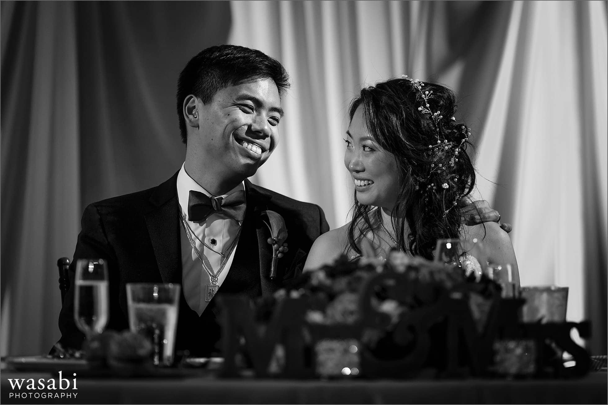 bride and groom smile at each other during toasts at Montgomery Club wedding reception